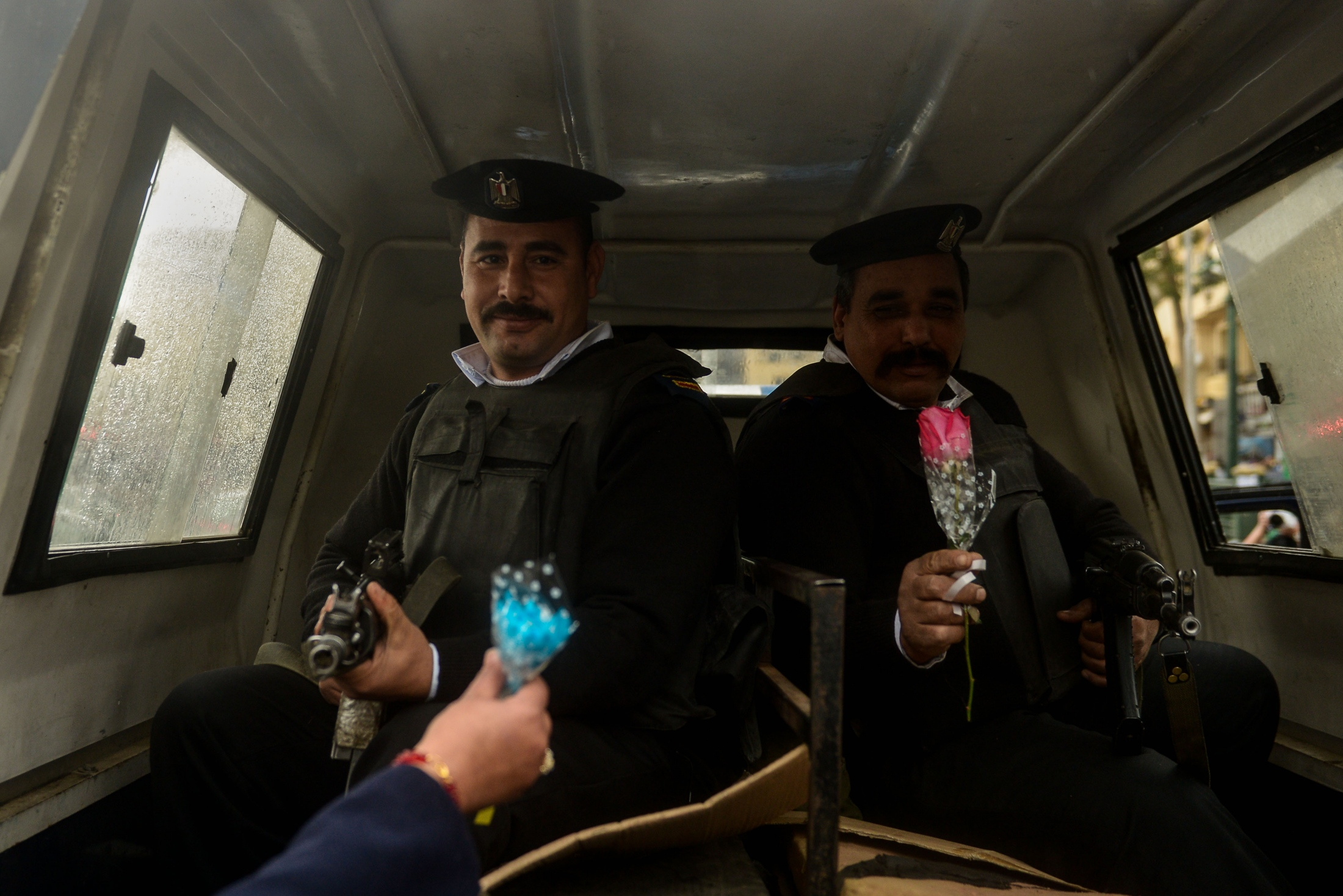 Egyptian policemen receive flower on Police Day, which falls on Jan.25. The day also marks the anniversary of the 2011 uprising in Cairo's Tahrir square, Cairo, Egypt.