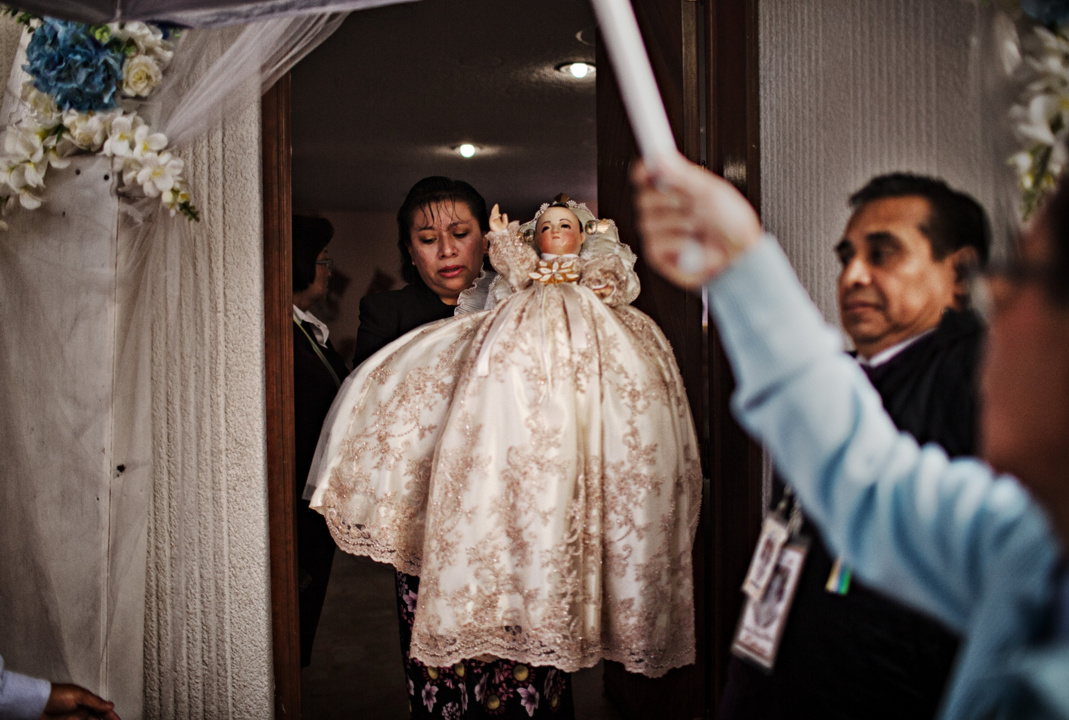 Niñopa is carefully held and protected from direct light as they exit Ms. Medina's home on their way to the cathedral to meet the new Majordomo. The Anthropological Institute of Mexico has determined that Niñopa, which is a 430 year old relic must be protected from direct sun light and flashes. Volunteers hold an umbrella to shield the Niño from sunlight.