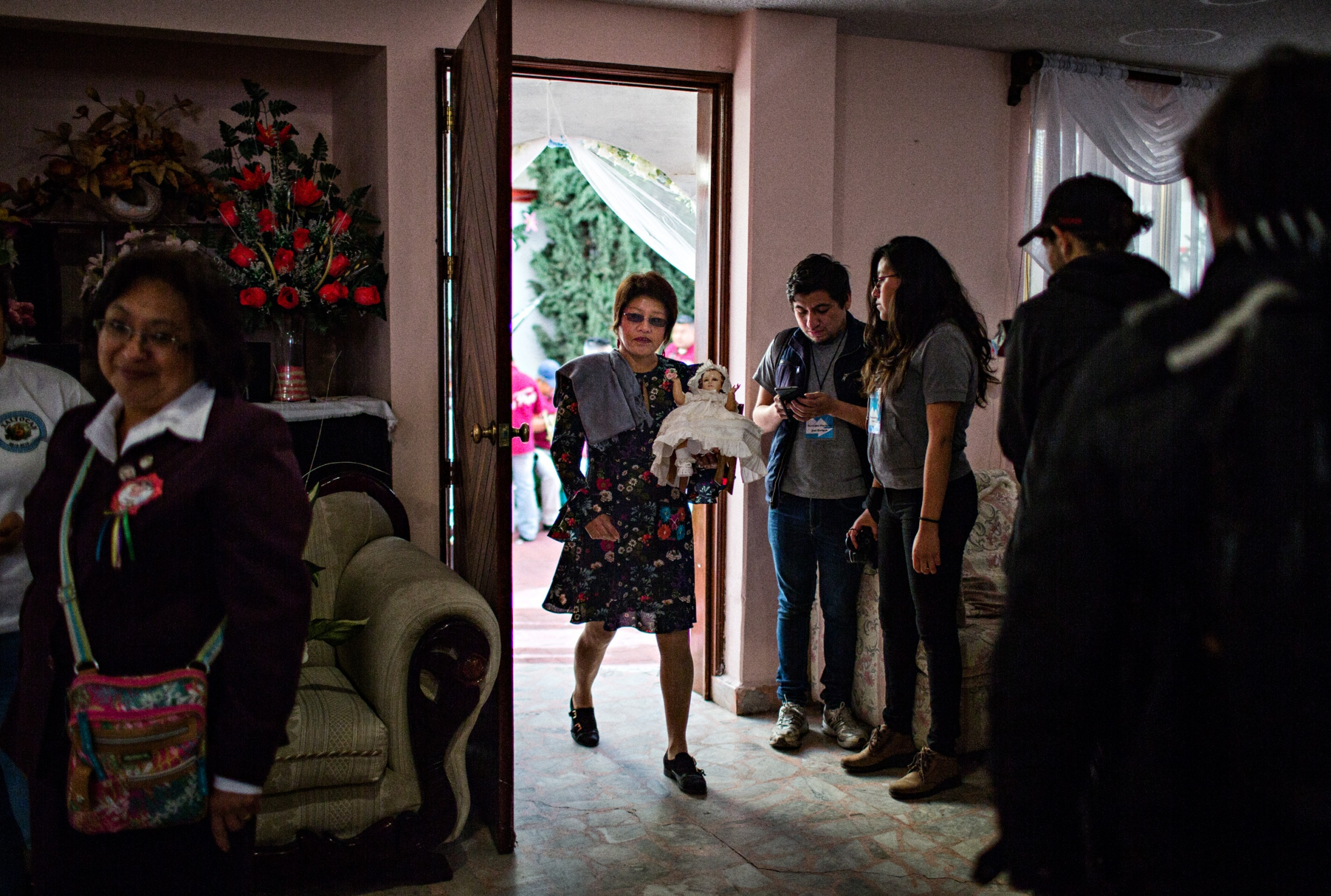 A woman holding a replica of Niñopa enters the living room where the Niño is displayed for worship.