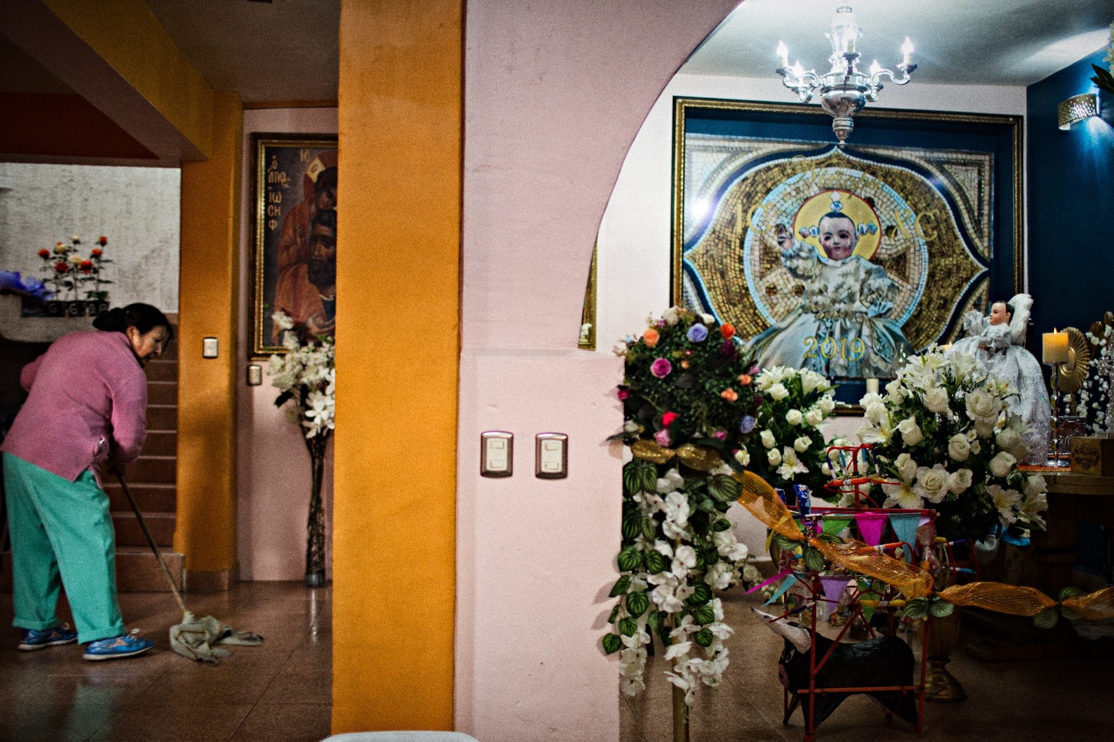 Many neighbors share in helping Niñopa's stay at the home of the Majordomo. A neighbor mops the floor before the doors are opened for the worshipers to arrive.