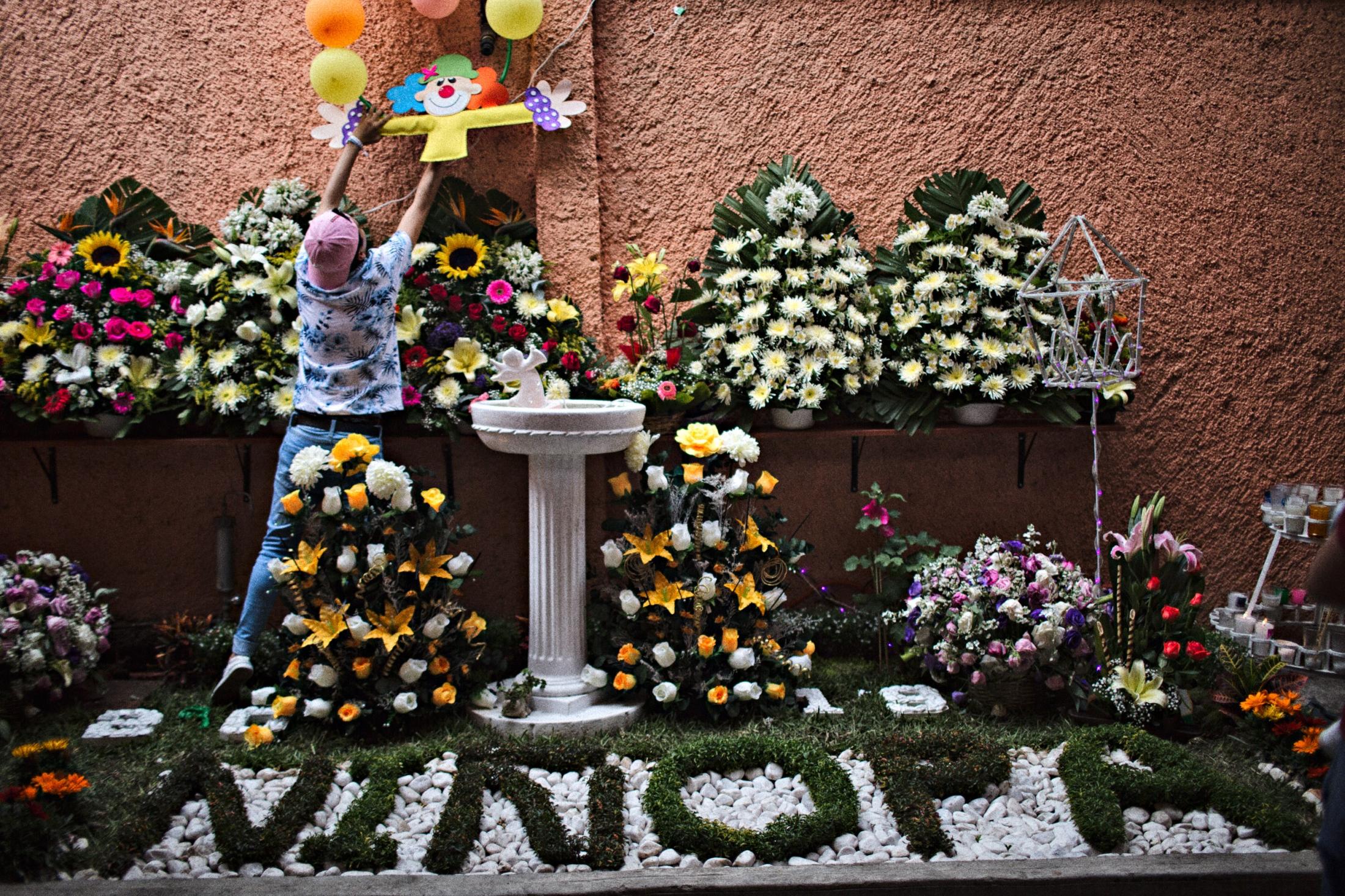 A boy places some balloons on the wall above a garden specially made for Niñopa.