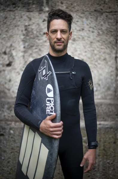 Local surfer Alex Neumann: 'This wave has changed my life in terms of friendships, work and love. It builds character as you have to learn to not give up, to keep trying until you can master the Eisbachwelle'. Outside the Haus der Kunst art museum at the Eisbach, Munich, Bavaria, Germany.