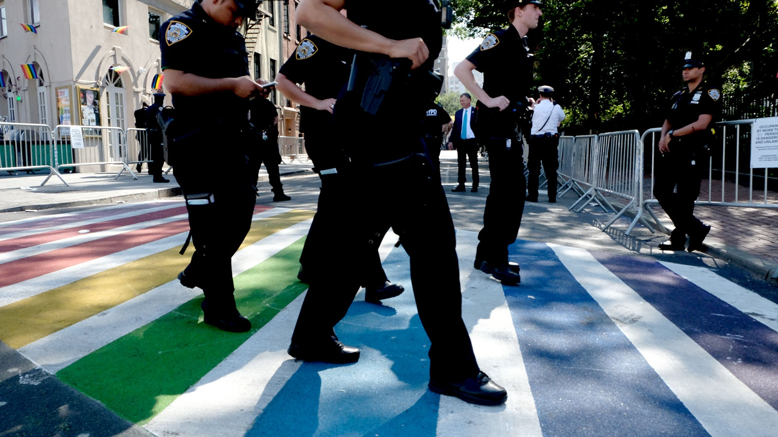 NYPD Officers wearing Blue walk over a rainbow painted crosswalk on Christopher Street and Seventh Ave near the Stonewall Inn early Friday morning the day marking the Fifty Anniversary of the Stonewall Riots.