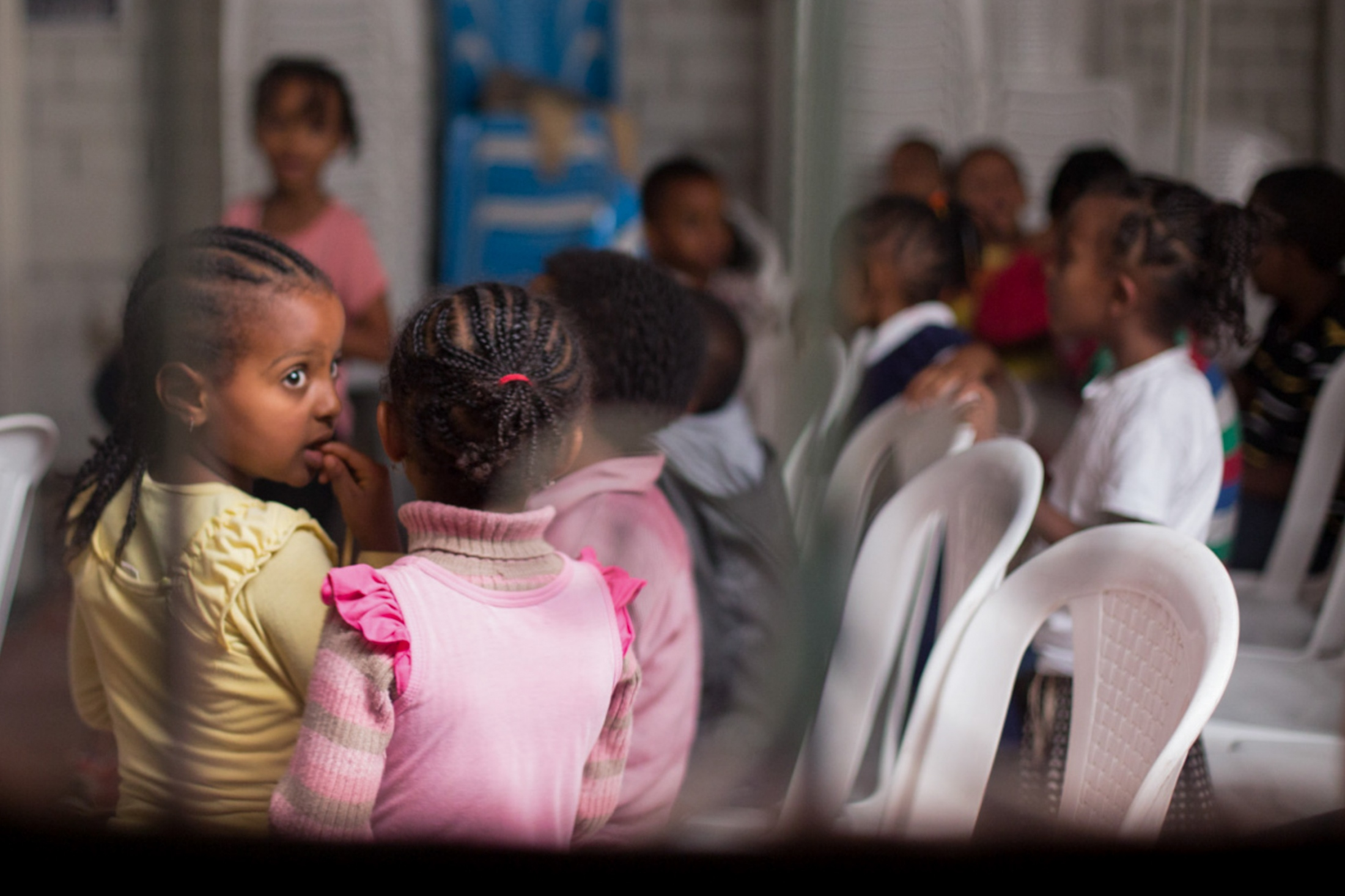 The place of sanctuary, a look into the main building of the community living on the outskirts of Addis Abba. It is being used as an afternoon music lesson for younger children. This photograph was taken from outside through some barbed wire put up to protect the community from xenophobic attacks. Fear of the other is deep-rooted in Ethiopia.