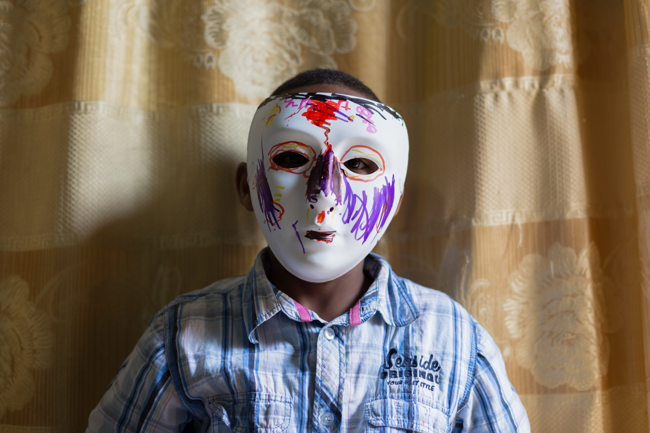 The portraiture of the children was shot in the building. It was designed around masks and art. A mask removes individuality; the plain mask represents the stereotypical, impersonal images produced en masse of refugees. The children created their own photograph, decorating over the plain white masks with complete freedom, adding personalisation to each image, and this allowed space for greater self-representation. The interactive nature of the portraiture allowed for the process of documentation to be slowed down. It also simply made sitting in front of a large camera less intimidating and more fun. In turn, I find these little things help to reduce the emotional barrier that exists between the photographer and the subject.