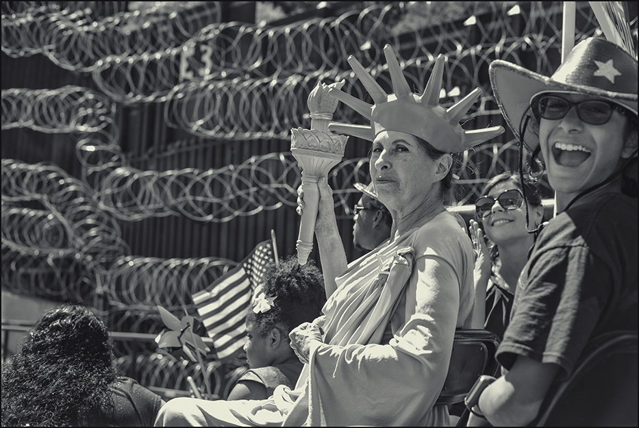 """Lady Liberty"" shows a smirk-- razor wire covered border fence (USA/MEX) in background. 4th of July parade, Nogales, Arizona. 2019."