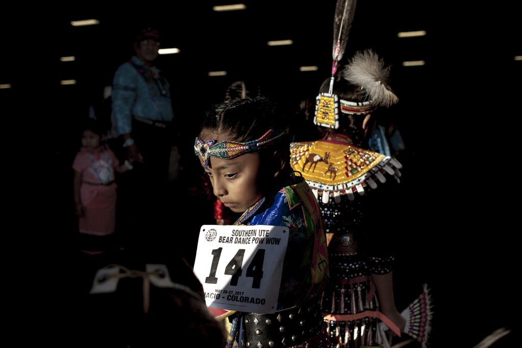 A little girl waits for her turn to go on stage at The Southern Ute Bear Dance Powwow. It is during these three days that the Ute Tribe gathers to celebrate the coming of spring, symbolized by the bear coming out of hibernation. Ignacio, Colorado.