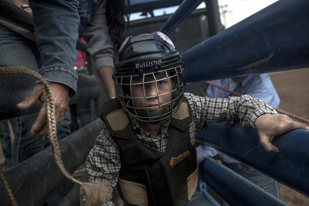 """A young kid prepares for a mutton bustin' (sheep-riding) competition at """"Spring in the Valley Rodeo."""" Alamosa, Colorado."""