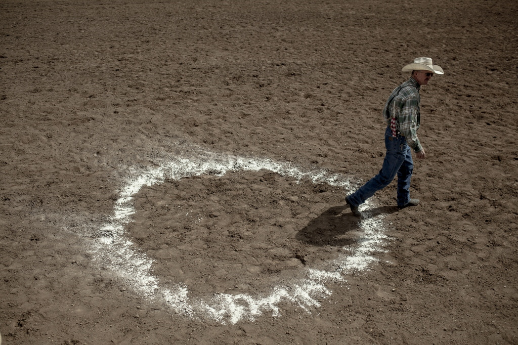 "A man prepares the field for a new competition round in the ""Spring in the Valley Rodeo."" Alamosa, Colorado."