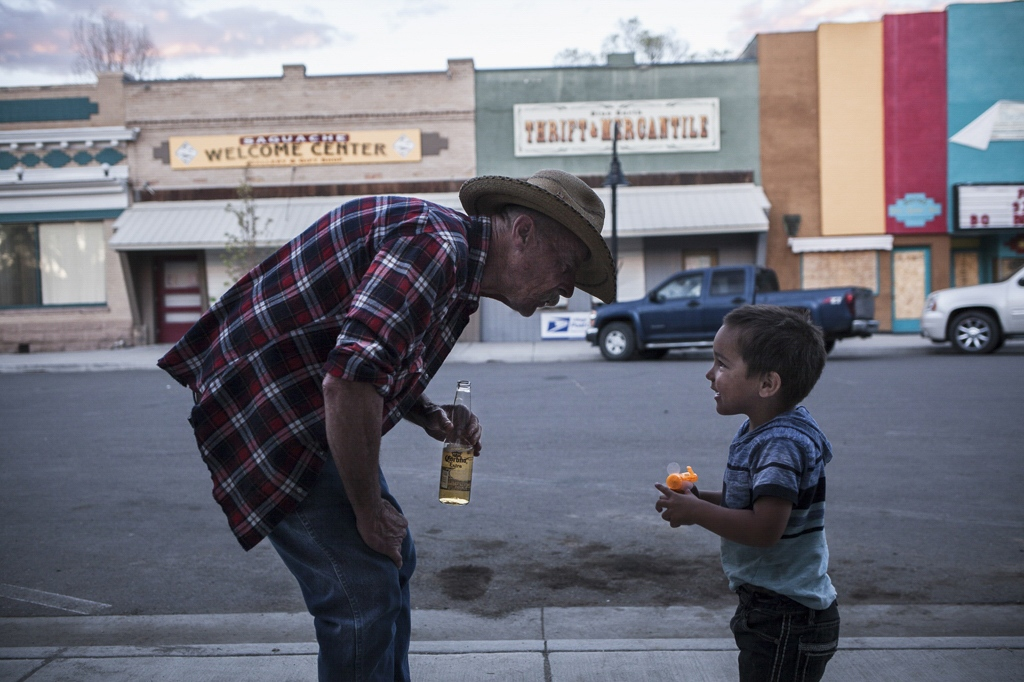 Buck, a Vietnam veteran from Texas, plays with a little boy, during a Cinco de Mayo celebration. Saguache, Colorado.
