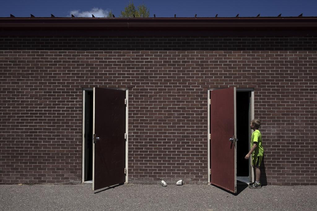 Kids entering the classroom after recess. Saguache, Colorado.