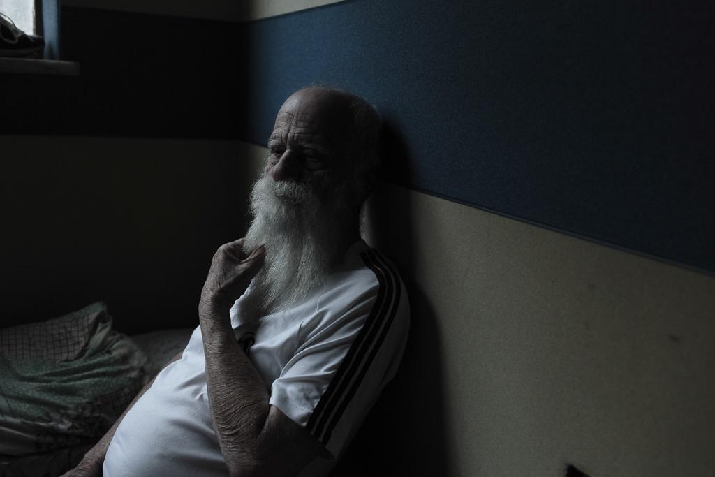 An elder man rests on his bedroom.