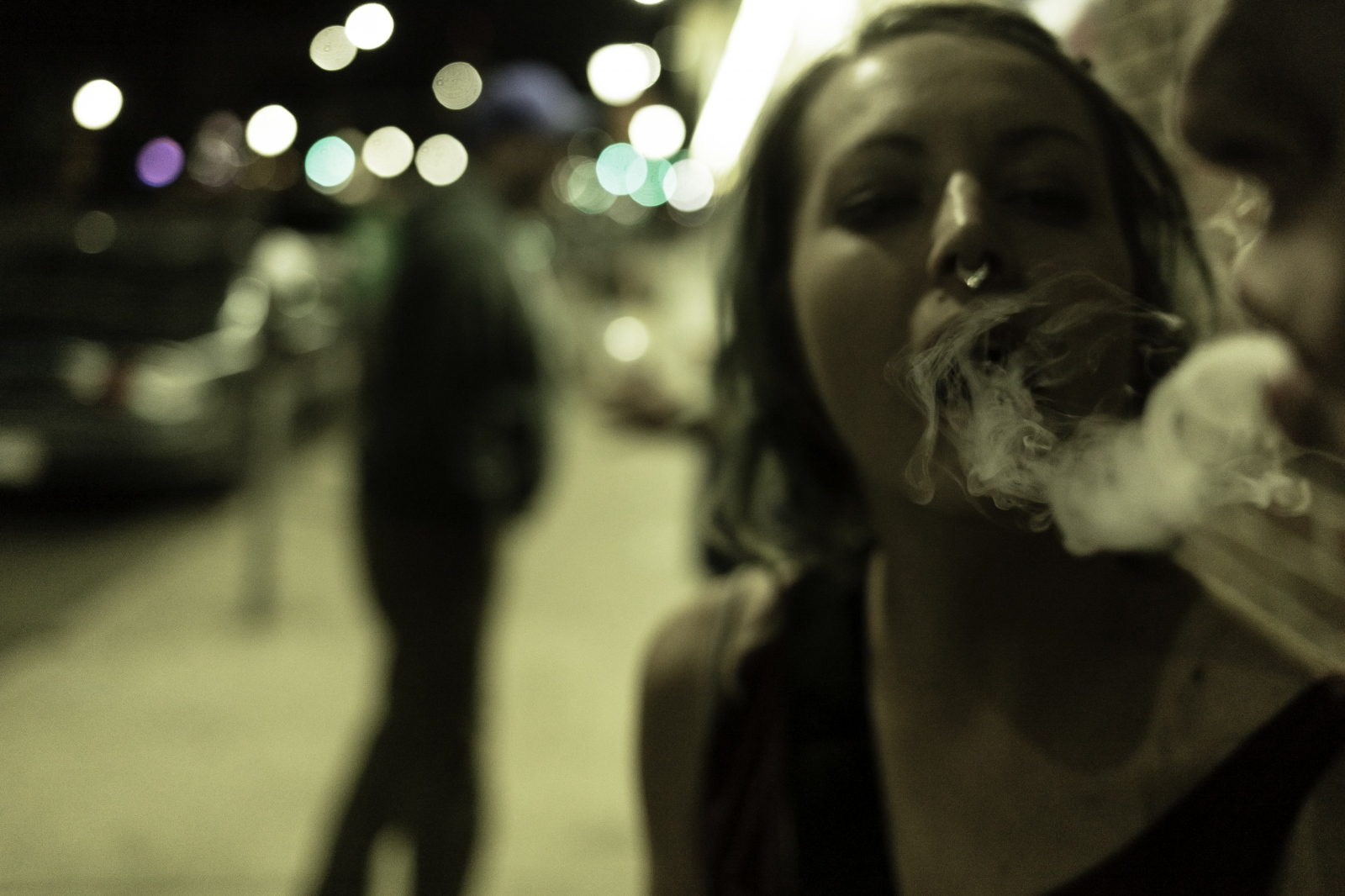 A couple of girlfriends share a marijuana joint outside of a nightclub in Colfax Av.