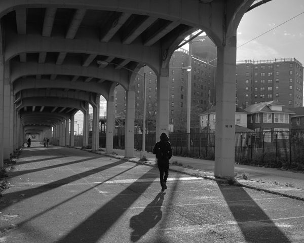 A young boy walks over Arverne, a street that remains closed underneath the train railway system. New York, 2019.