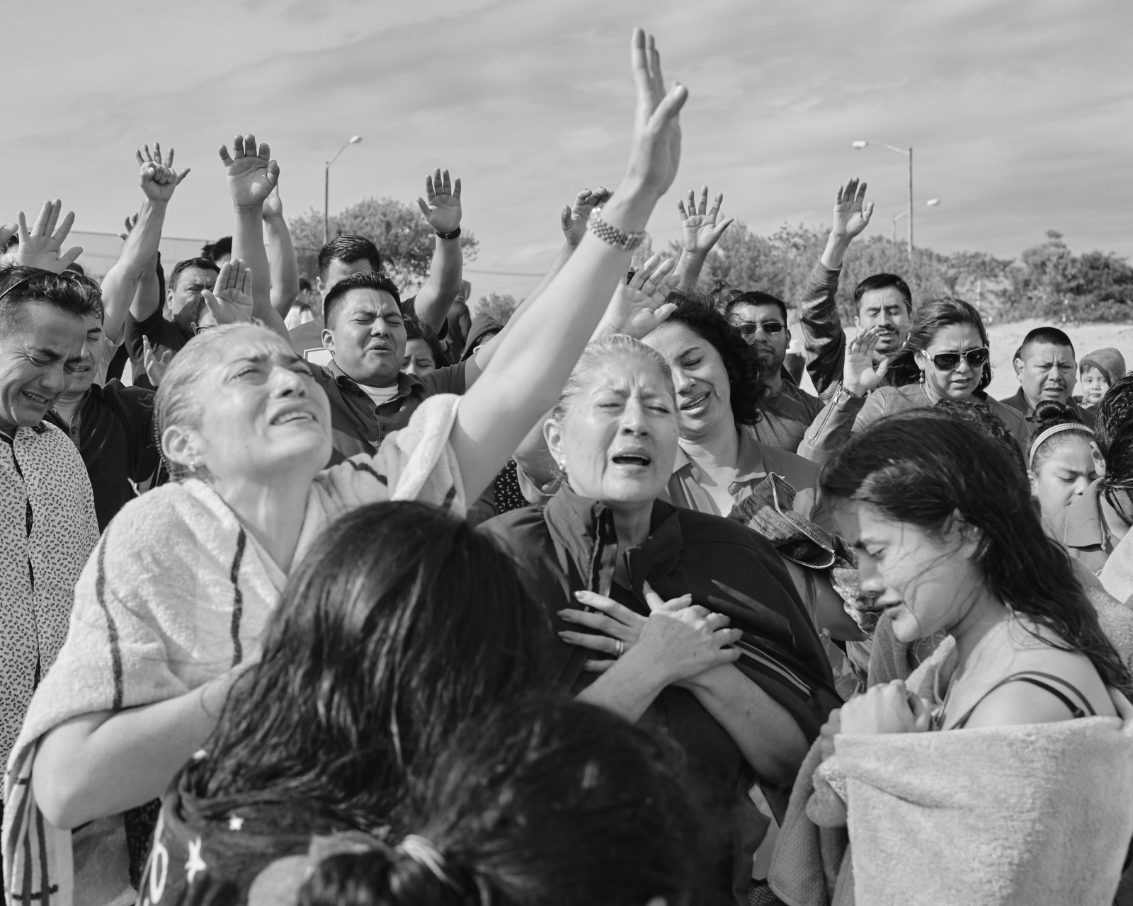 A group of evangelical prays to the heaven in celebration of baptism in a Sunday morning, over the Reynolds Channel in Far Rockaway.