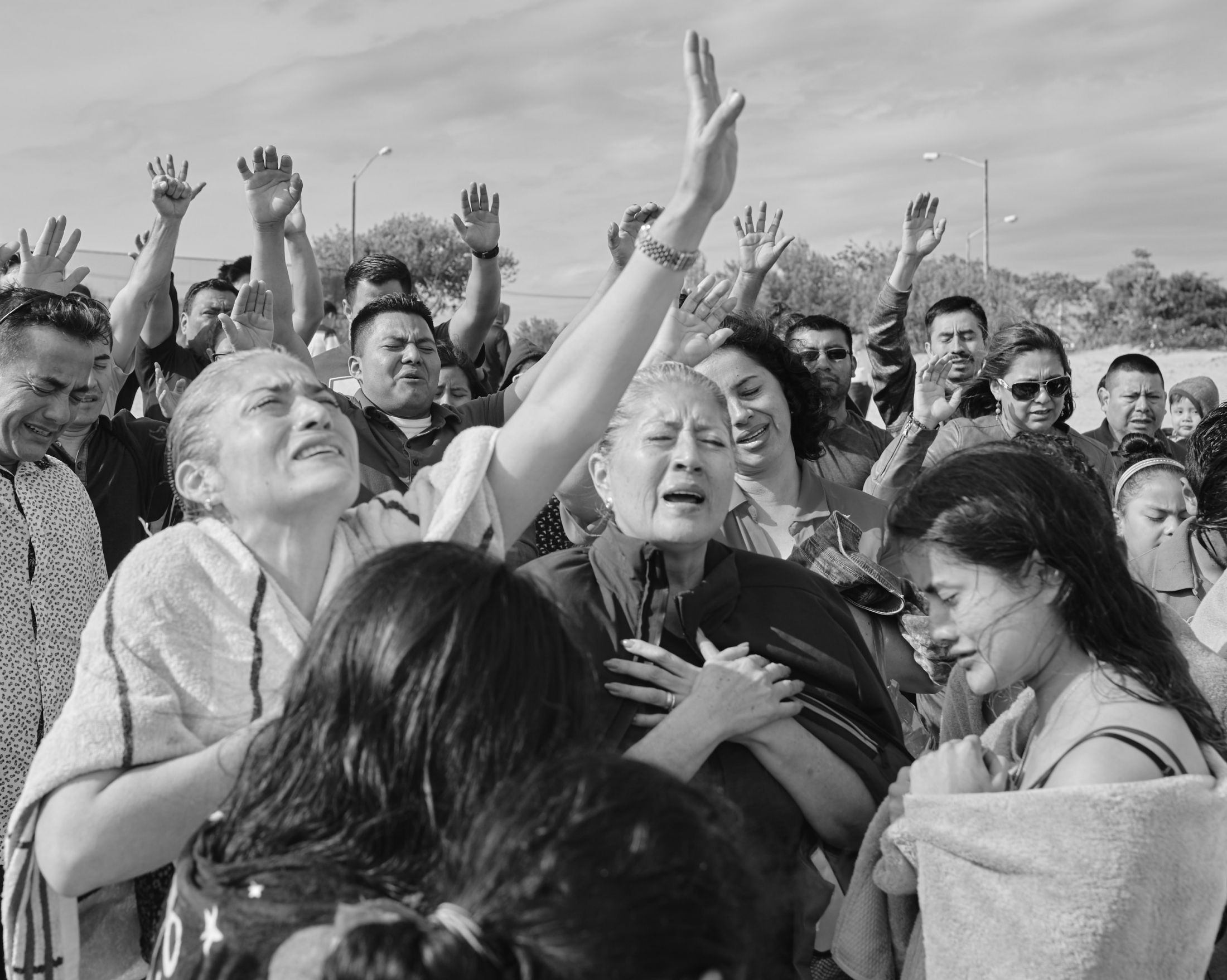 A group of Mexican evangelical cheers to a baptism celebrated over the Reynolds Channel in Far Rockaway. Different groups, coming from Queens, Bronx, and even nearby states,  uses the Rockaways a shared space to celebrate their religious beliefs. New York, 2019.