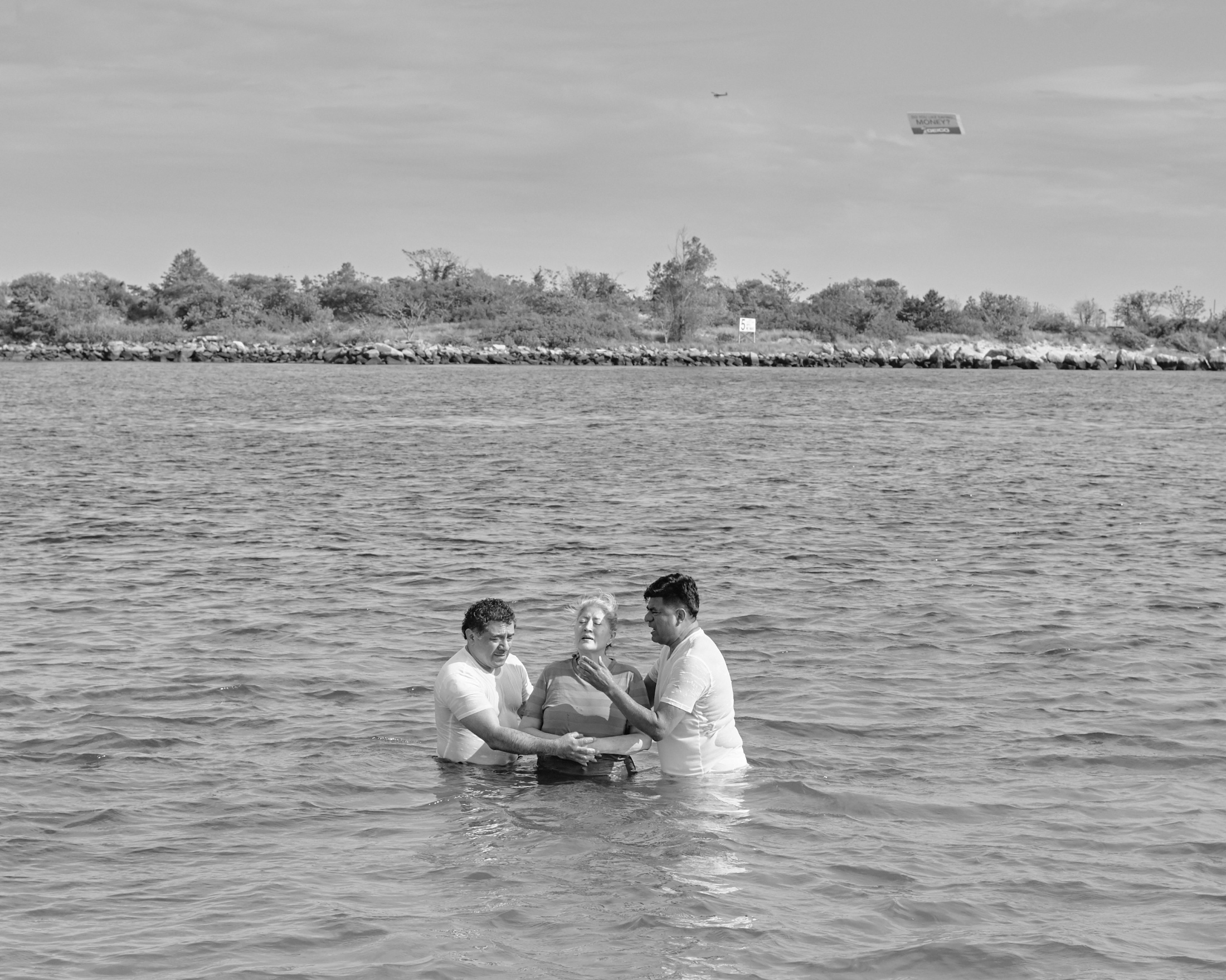 A group of evangelical celebrates a baptism in a Sunday morning, over the Reynolds Channel in Far Rockaway. New York, 2019.