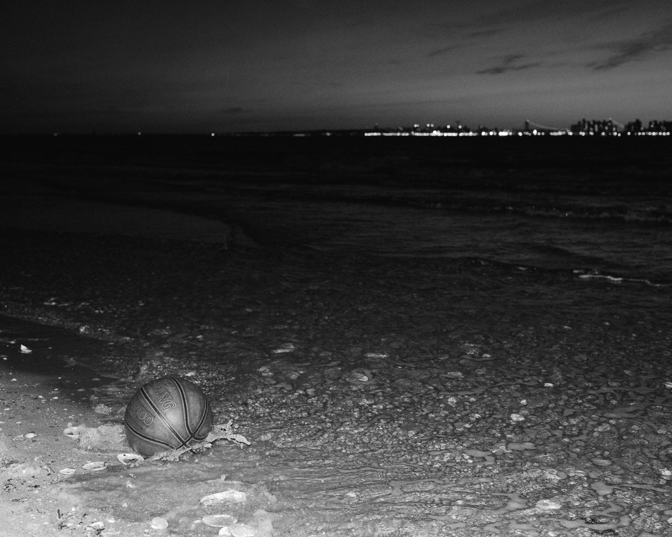 A castaway basketball floats on the shore of 'Breezy Point' in the western side of Rockaway beach, with a view to Fort Hamilton area in Brooklyn. New York, 2019.
