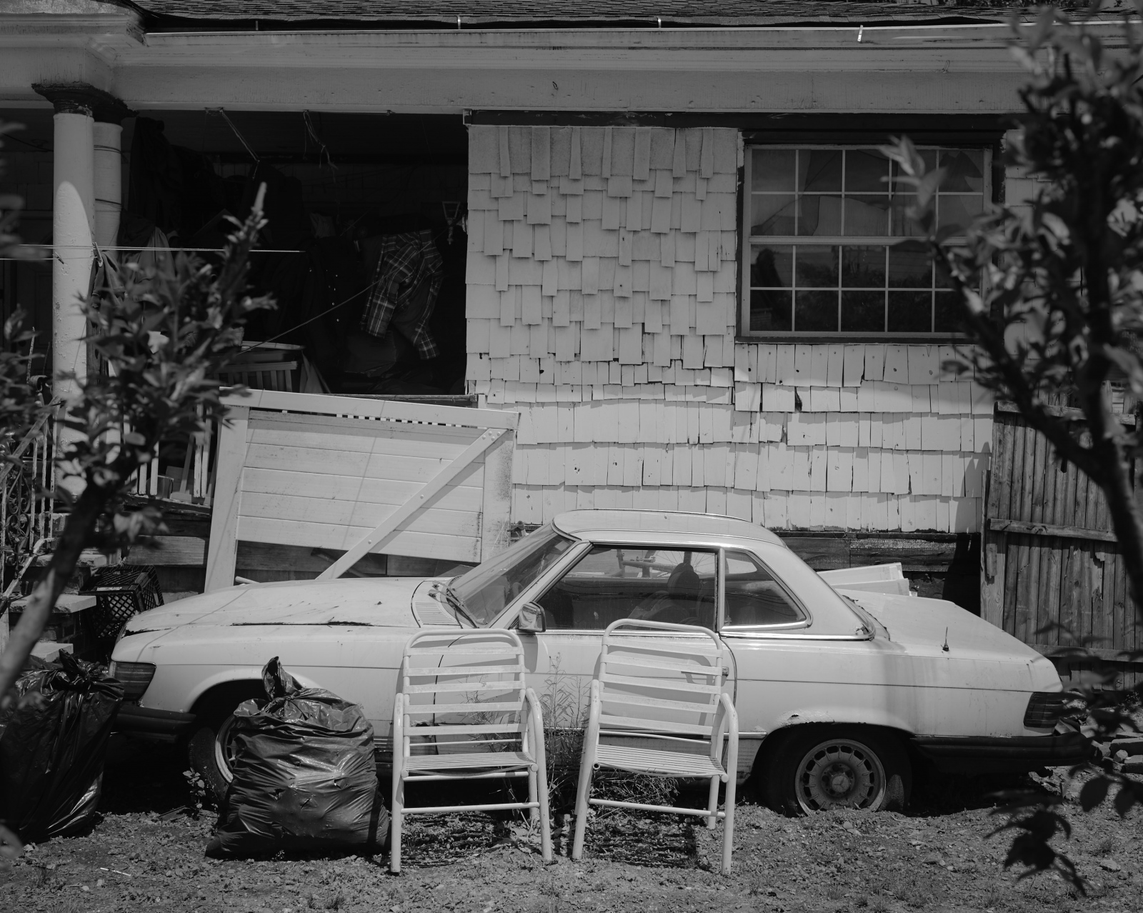 A broken car parked in the porch. Even though most all the houses are already repaired or demolished and rebuild, there are still some people that never throw away their most precious belongings.