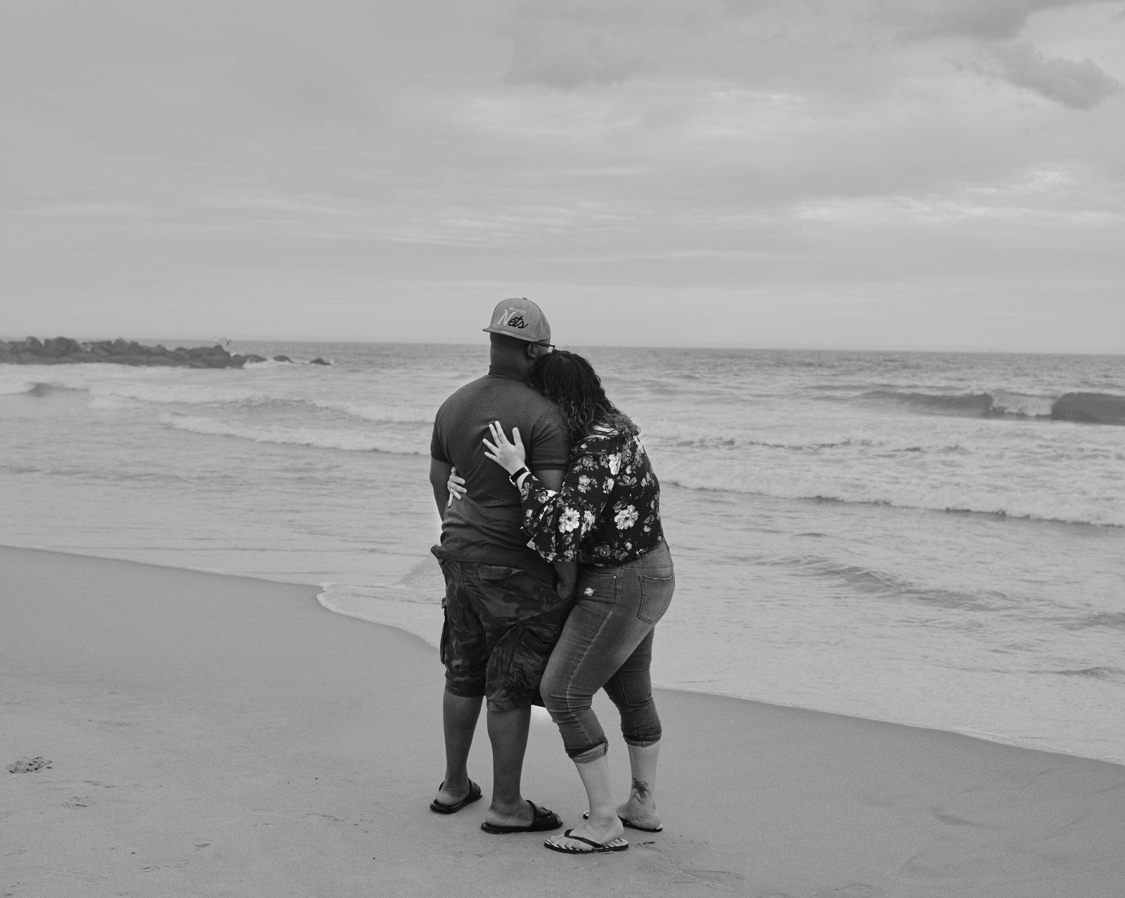A couple snuggles in front of the ocean.