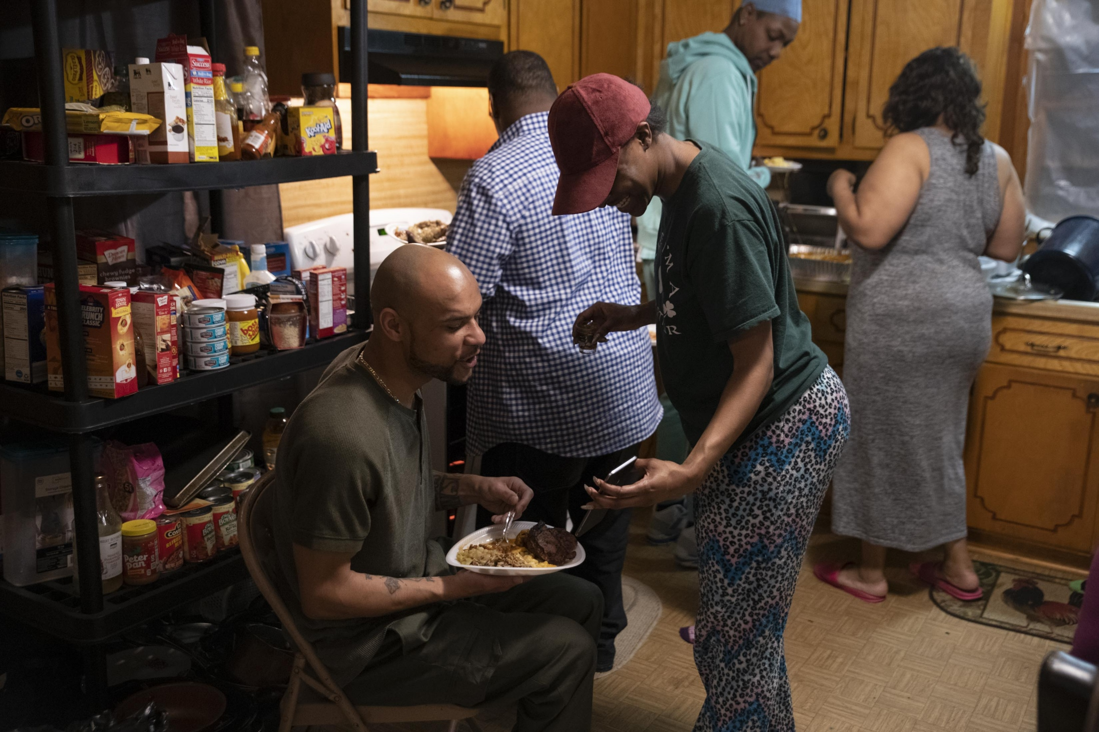 Family gathers for a welcome home dinner at Walika's house in Kannapolis. Oriana helps her uncle learn how to use his Iphone. He never used a smart phone before going to prison.