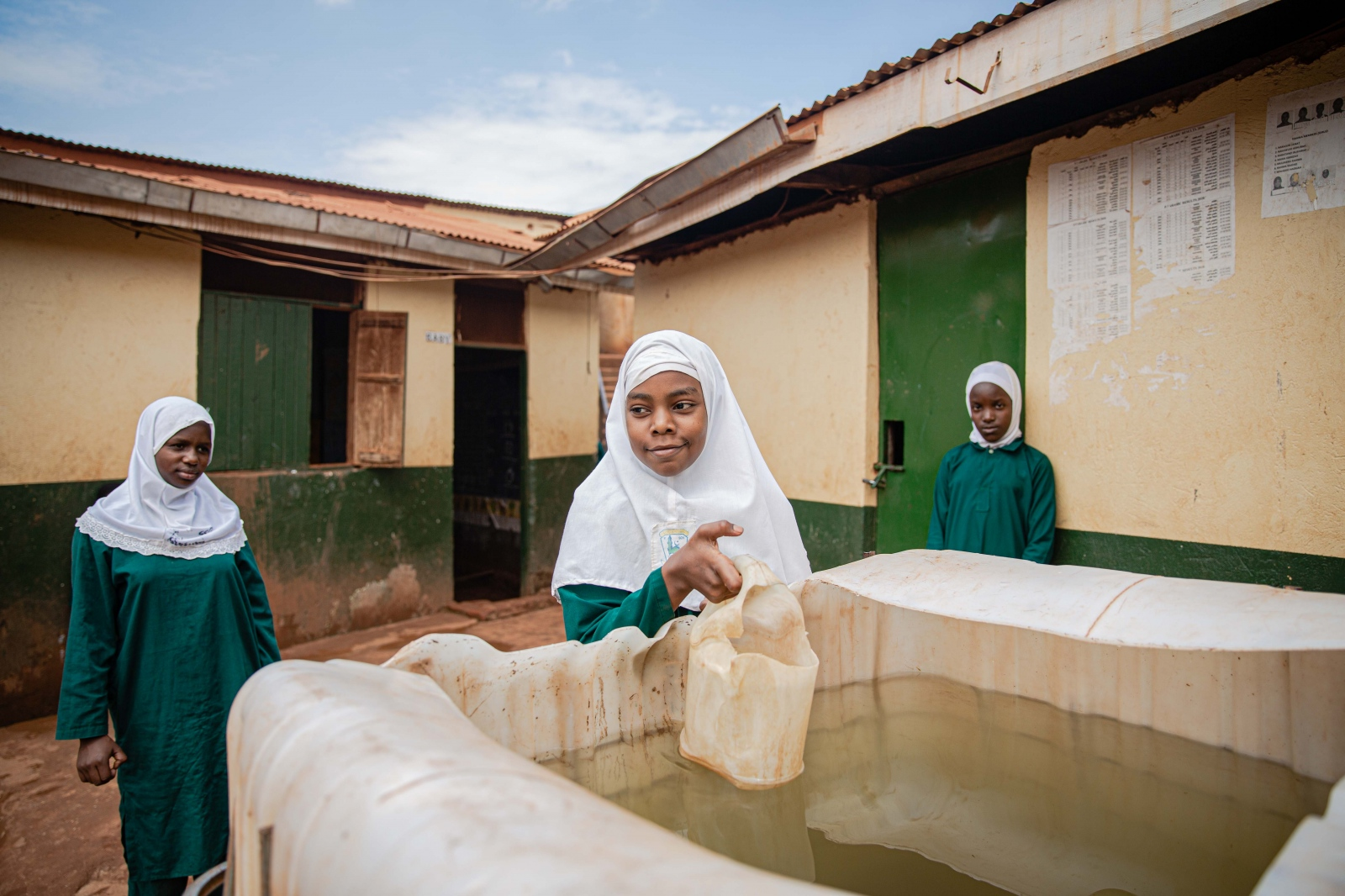 Baitha, a primary six pupil at Lufuka Islamic Day and Boarding Primary School collects water for ablution.  The school pumps water into the big water tanks so that its safe for children to access during the day.  For Agence Française de Développement
