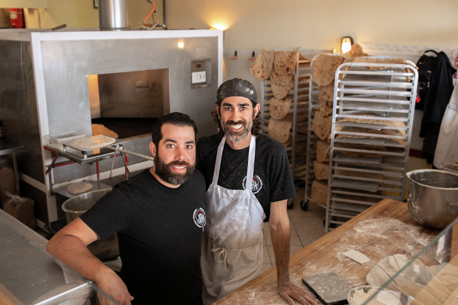 Brothers Jaymes and Jayson Khademi stand flour-covered in their Saffron Jak kitchen in Phoenix, Ariz.