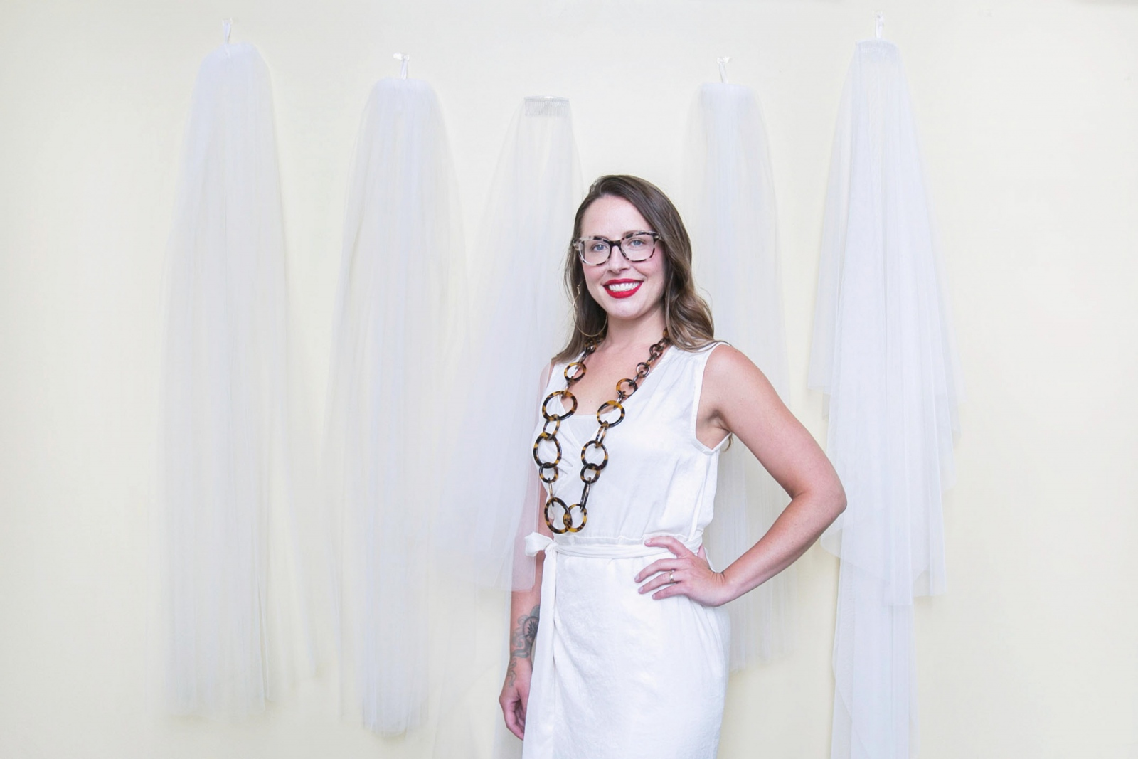 Ali Eagen, a custom wedding dress designer who owns made by anatomy, wears a few of her favorite things in her studio at Hotel at the Lafayette. On the wall behind her are fabric samples for veils.