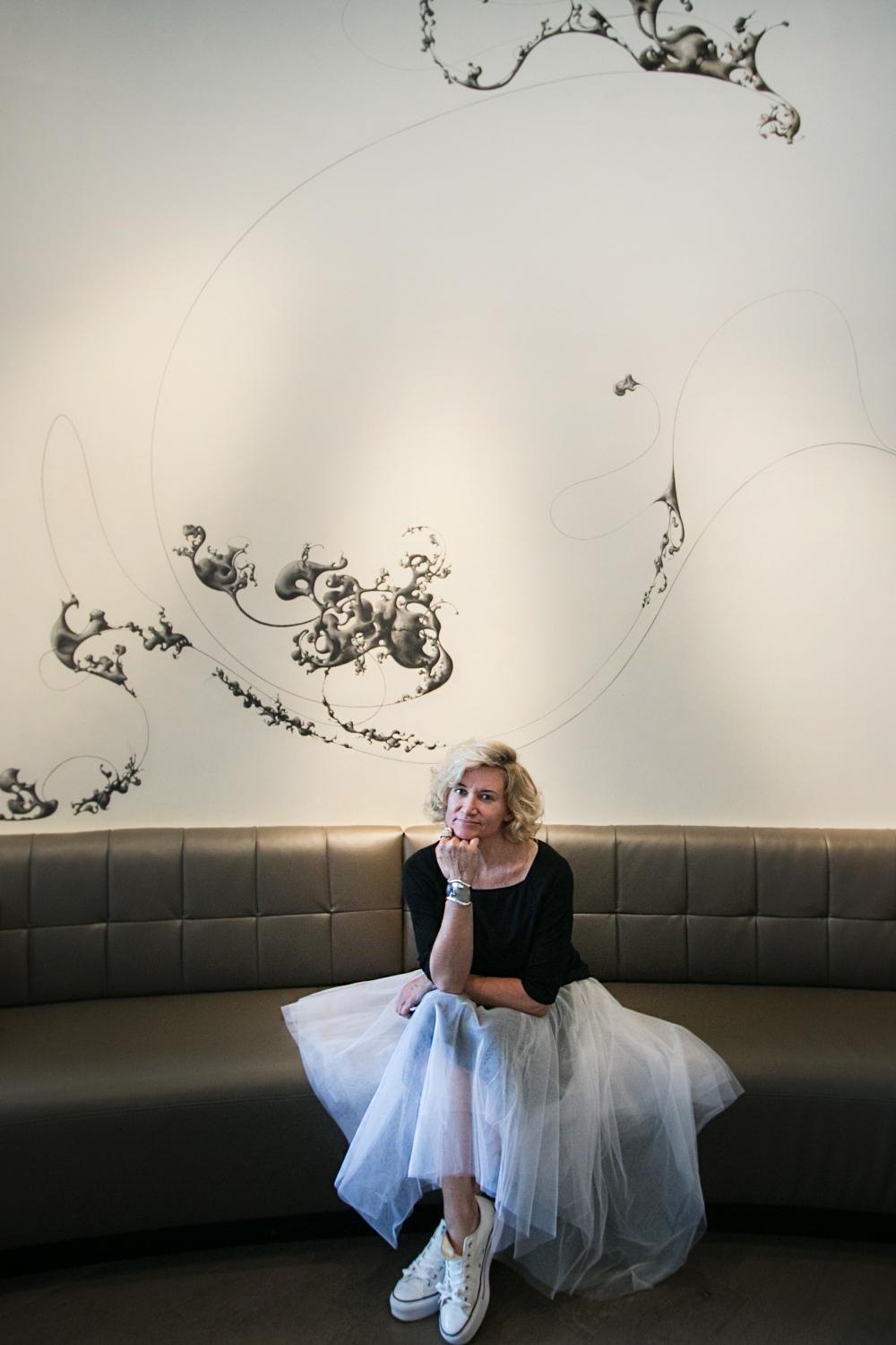 Buffalo artist Fotini Galanes is photographed in front of one of two 20-foot-high murals she created in the lounge at Patina 250 on Delaware Avenue. It's a freehand charcoal drawing done directly on the wall.