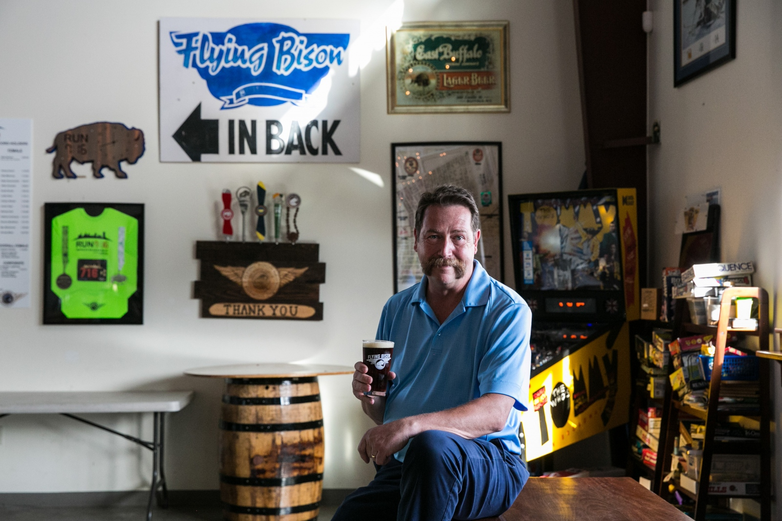 Flying Bison founder Tim Herzog sits in front of the brewery's oldest sign with a glass of Aviator Red in his hand in Buffalo, N.Y.