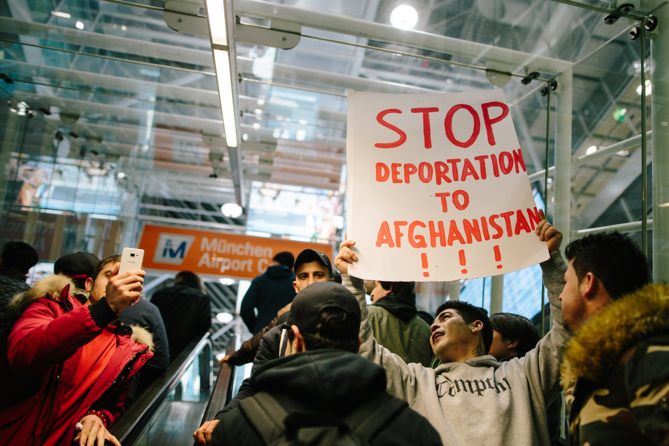 A young man carries a sign calling for a stop of deportations to Afghanistan at a protest at Munich airport. February 22nd, 2017