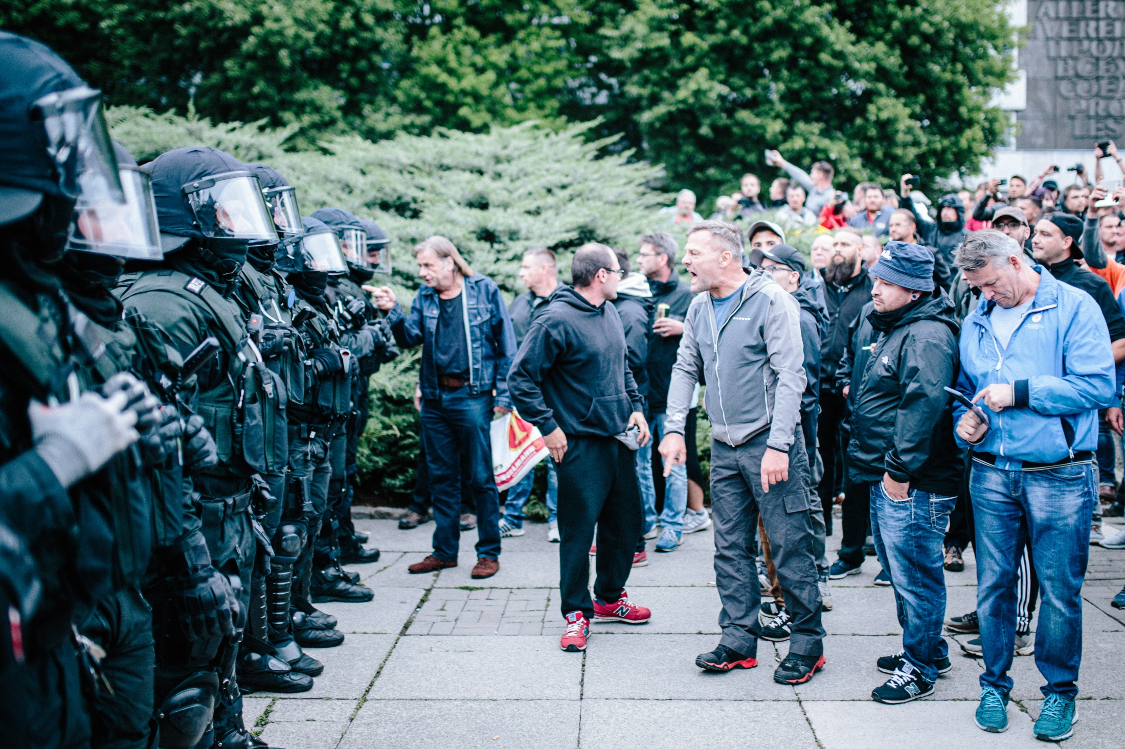 Far-right demonstrators shouting at police holding back the group after street blockade.