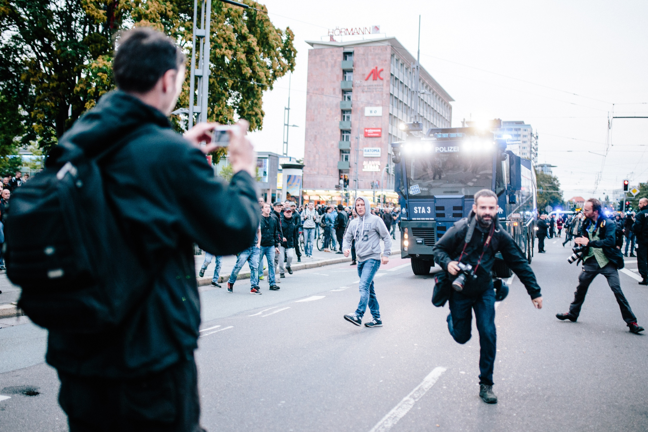 Journalist running away after attack by protester.