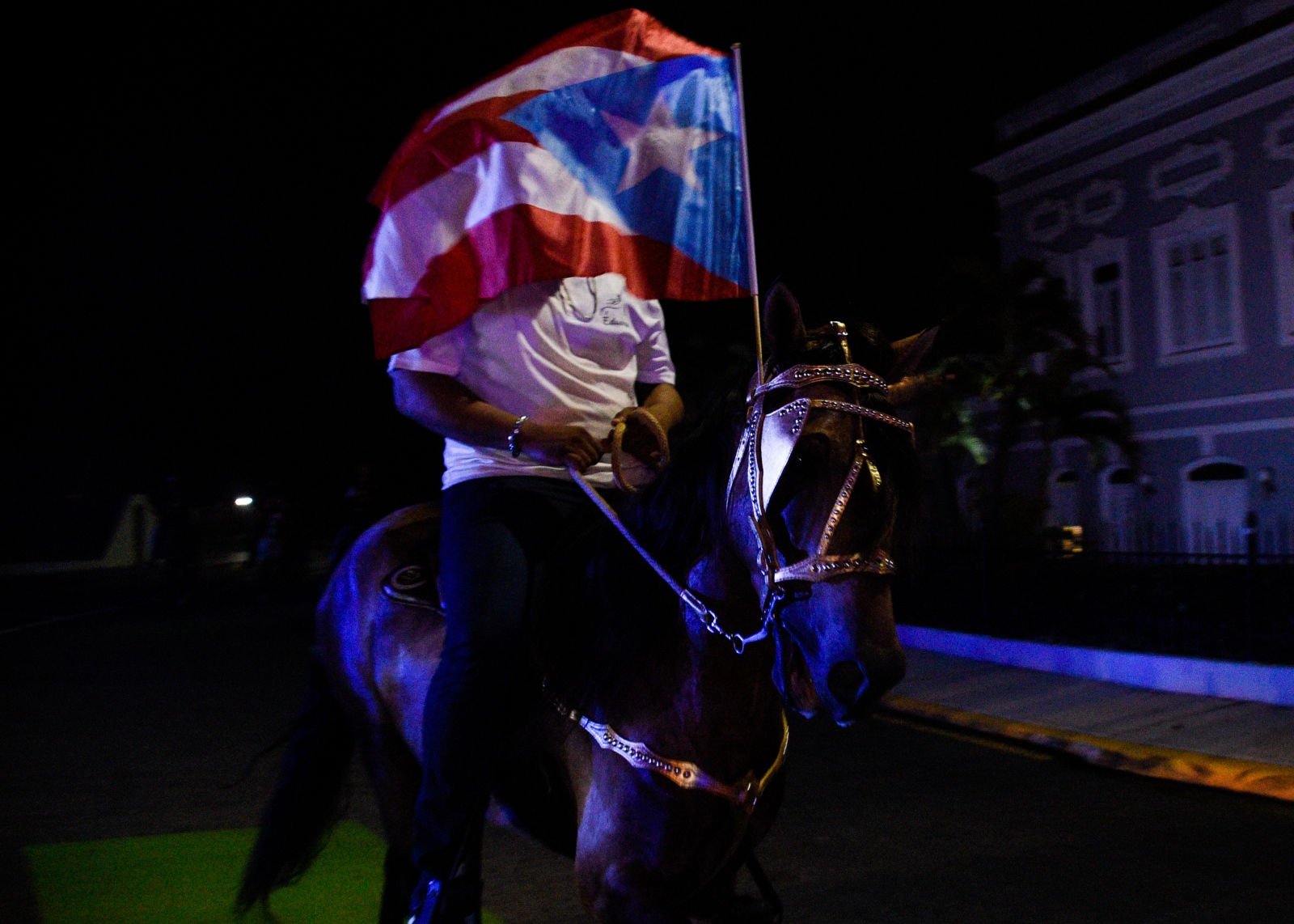 Demonstrators on horseback wave Puerto Rican flags during the protests calling for the resignation of Governor of Puerto Rico, Ricardo Rosselló. Shot while on assignment for Reuters on July 16, 2019.