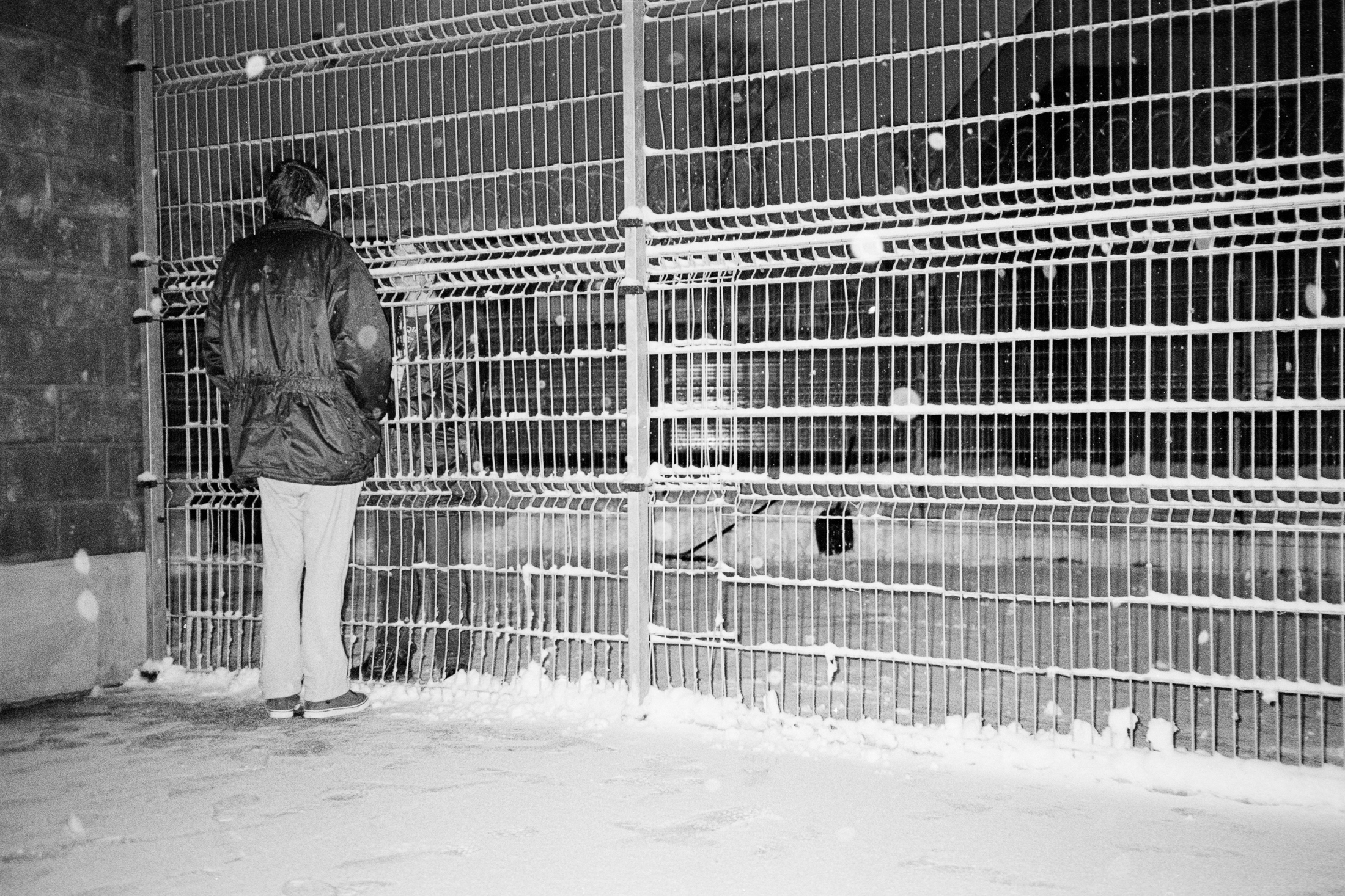 Here through a fence separating spaces of the prison, two inmates discuss. One of the detainees' tasks is to clear the snow from the aisles.