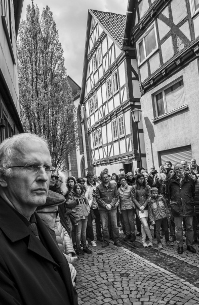 "Crowds gather to watch the Stolpersteine  Ceremony at Treysa, in the German District of Schwalmstadt.  Gunter Demnig (72) conceived and initiated the 'Stolperstein' art project; 'An art project that commemorates the victims of National Socialism. Demnig  often cites the Talmud (the central text of Rabbinic Judaism and the primary source of Jewish religious law) stating clearly that ""A person is only forgotten when his or her name is forgotten"""