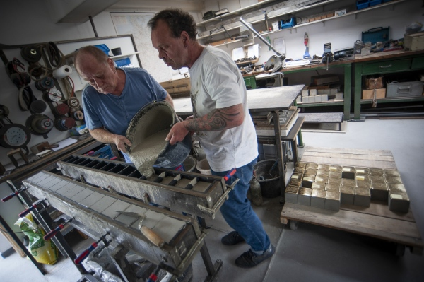 Sculptor Michael Friedrichs-Friedlaender and his assistant Asigora at work making Stolpersteine at the studio in Pankow district of Berlin, Germany.
