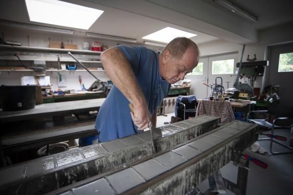 Sculptor Michael Friedrichs-Friedlaender at work making Stolpersteine at the studio in Pankow district of Berlin, Germany.