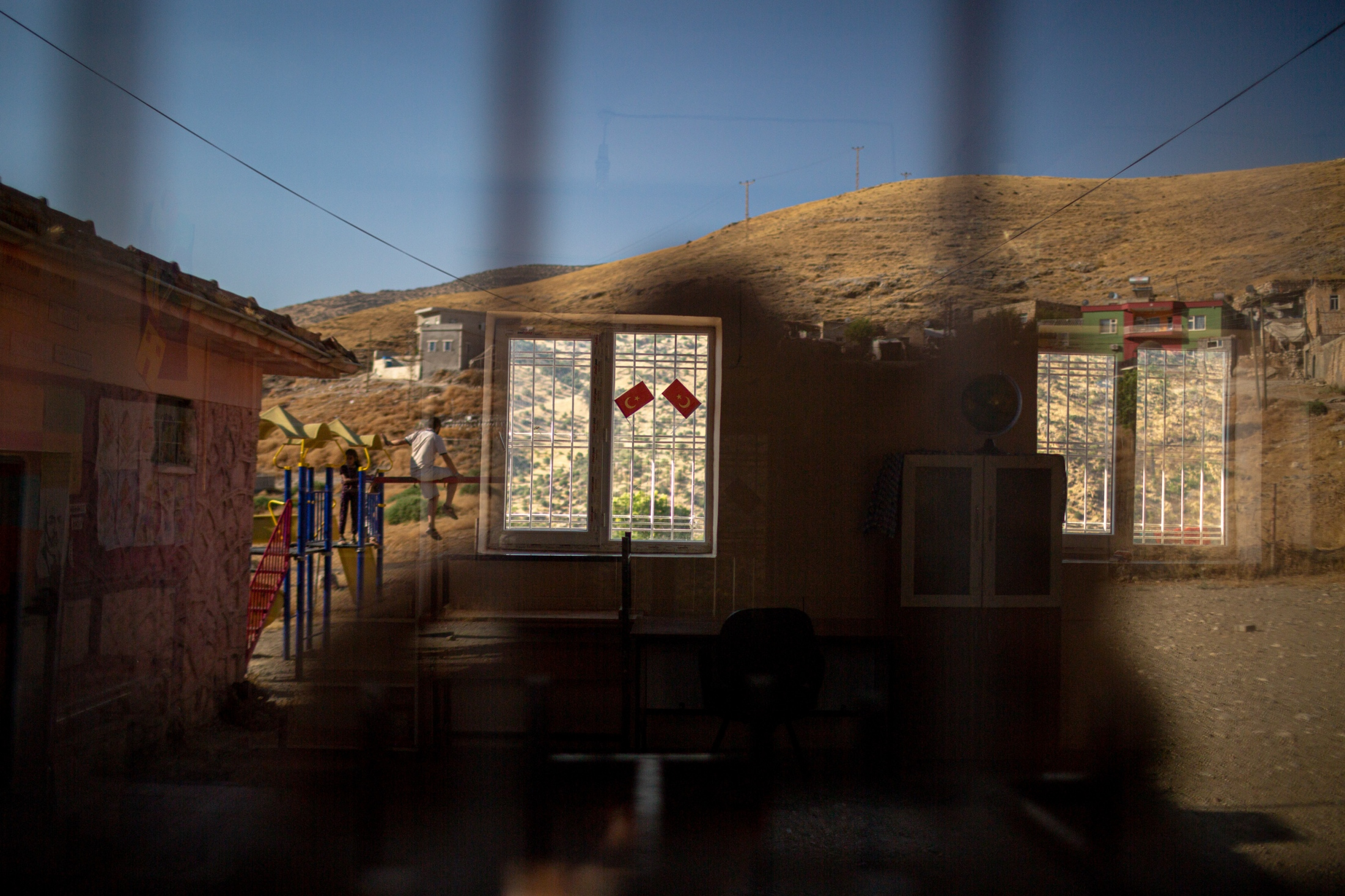 The reflection of a child on a school window during the summer break is seen in a village close to Hasankeyf which is located in the flood zone and is slated to be submerged once the dam waters arrive.