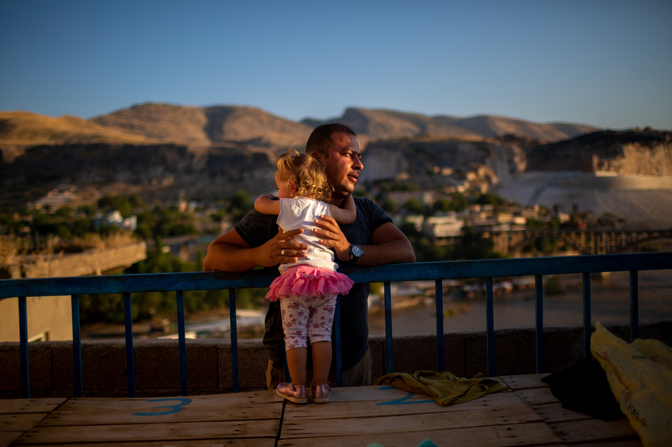 A father holds onto his young daughter in the village across Hasankeyf. While their village is not going to be submerged, due to destabilizing nature of the flood, they will have to move out of their village along with the residents of Hasankeyf. The future is unclear for these residents. As of early October 2019, the roads to Hasankeyf and surrounding villages will be closed.