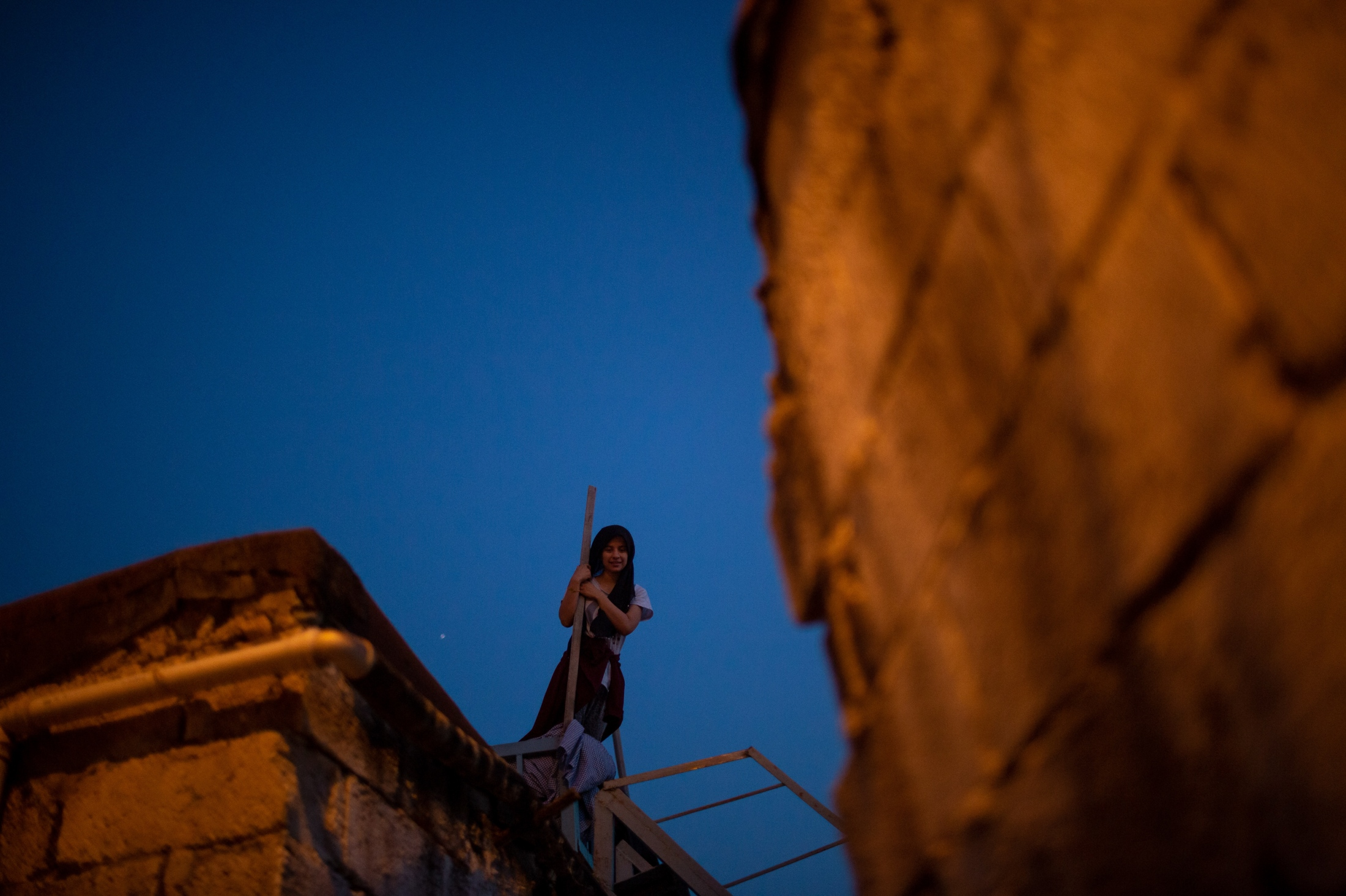 A young Kurdish girl playfully watches on from the roof of her home. Residents sleep outside on the roof of their homes during the summer when the air is warm and sleeping outside provides a relief from the heat.
