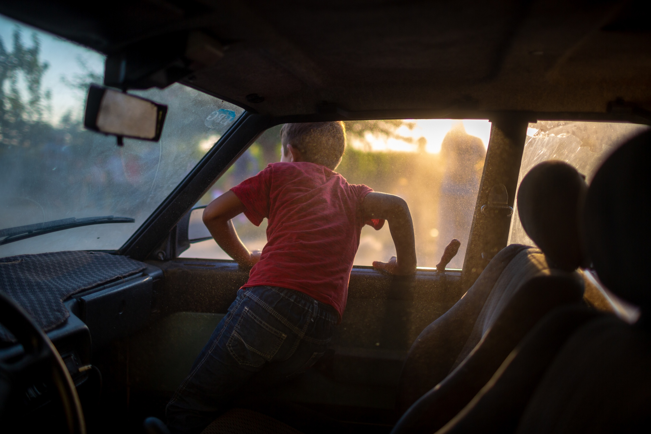 A young boy hangs out of the family car at sunset in a village near Hasankeyf situated in the flood zone.
