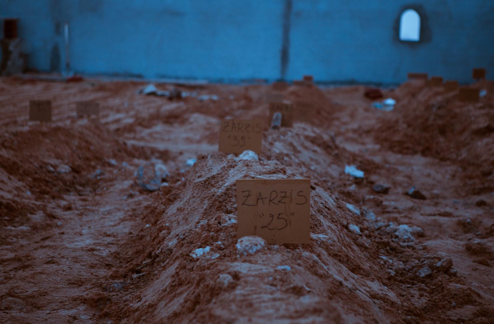 Une tranchée a été creusée, chaque emplacement est séparé par des briques. Des employés municipaux s'activent, masque hygiénique sur le visage et gants plastifiés. Ils portent en terre les dépouilles. Des pancartes en bois numérotées pour chaque sépulture