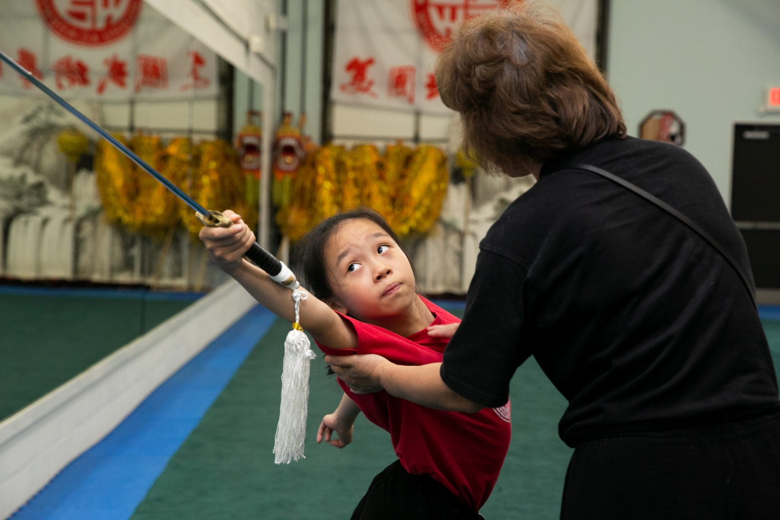 Twelve-year-old Jocelyn Gu practices her performance for the USAWKF National Team Trials while Zhang corrects her form.