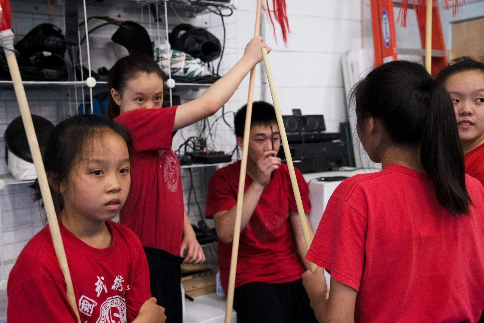 The advanced team, Jocelyn Gu, 12, Michelle Xiong, 14, Benjamin Tran, 15, Joanne Li, 13, Helen Gu, 16, listens to feedback from Zhang.