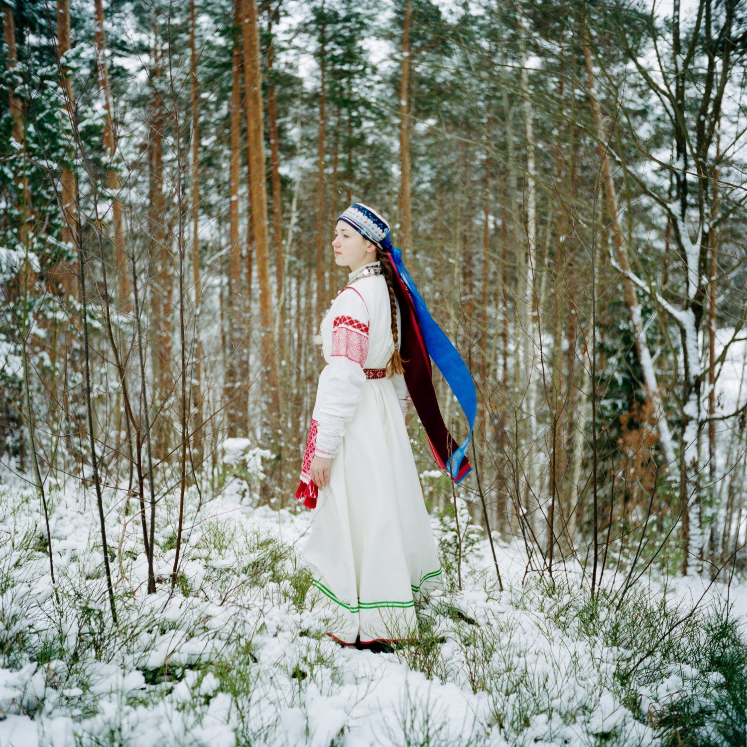 "In Obinitsa, Estonia, a young Seto girl named Liisi Lõiv pauses wearing a traditional costume in her grandparents' garden. Seto women typically have both an old costume and a new one. This is an older one—white, with long, rolled sleeves. The clothing reveals other details too. A married woman must cover her hair, while an unmarried young woman or girl like Liisi will wear only a garland or a headscarf, leaving her long braid visible. Today Setos wear their traditional clothes only on special occasions. Liisi says she embroidered this costume herself. ""I'm proud of being Seto,"" she says. ""It is where I come from, where I grew up."""