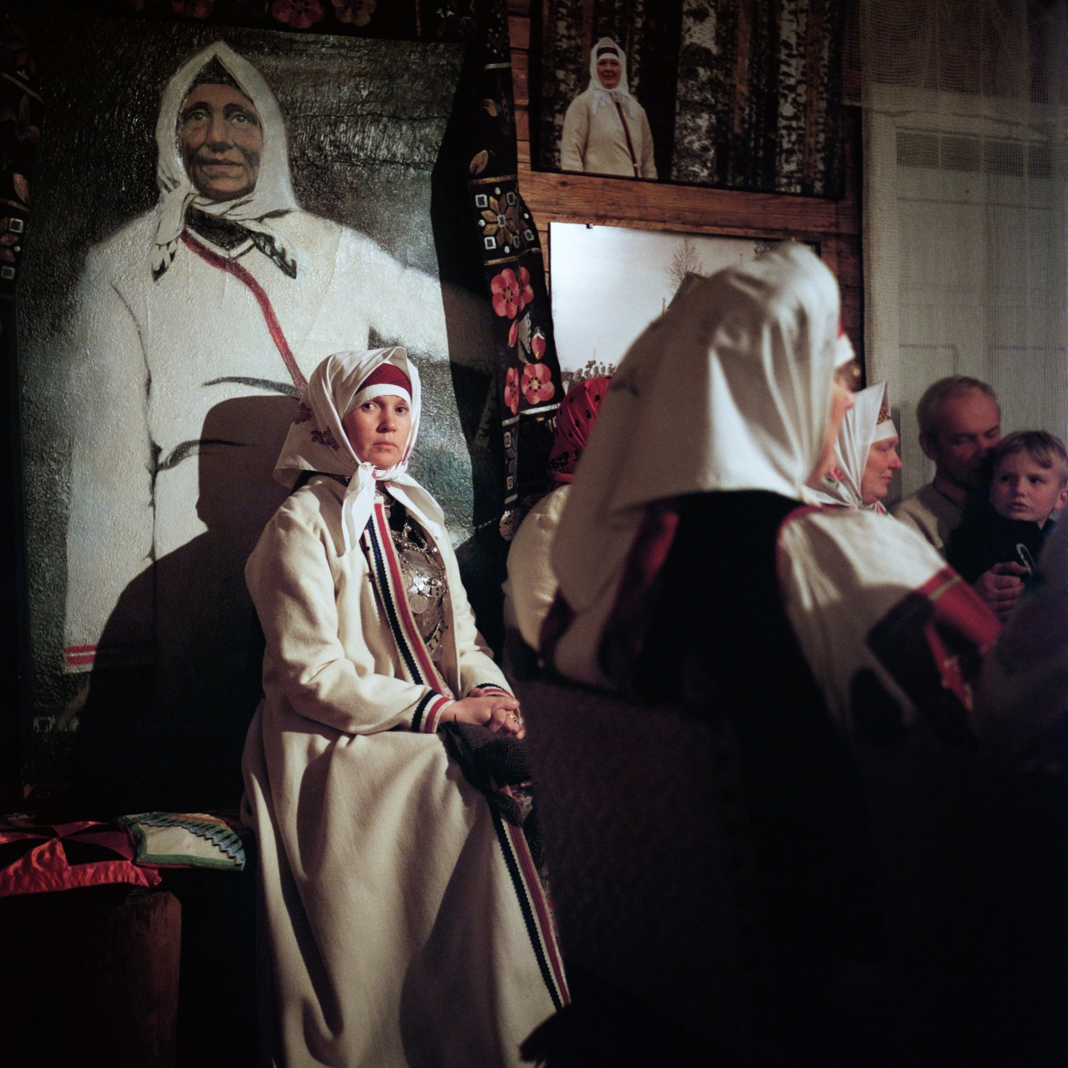 Marika Keerpalu, wearing a traditional costume at a small art gallery on the Estonian side of the border, welcomes a group of visitors from Mordovia, Russia. The visitors speak a language called Erzya that is similar to Seto. Wearing her hair fully covered signifies that Marika is married. Here, she sits below a painting of Hilana Taarka, a Seto woman from the turn of the 20th century famed for her rebellious singing.