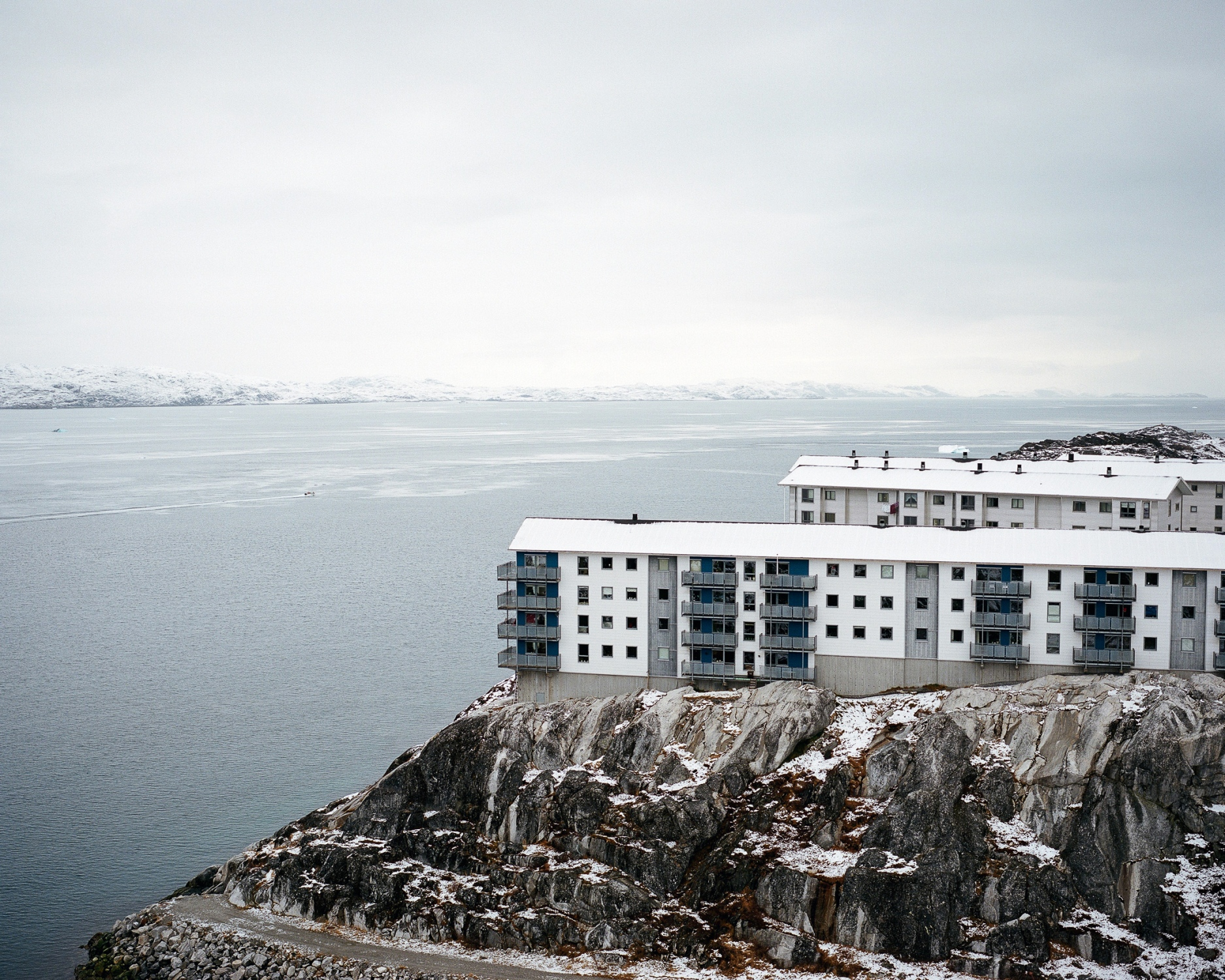 Residential building in the capital Nuuk. Nuuk is the administrative center of Greenland in habited by 15.000 people.  Nuuk has got over the recent decades a fast growth of its population. During the seventies many Greenlandic settlements were shut down and their inhabitants moved to Nuuk. This concentration politic has been stopped in the 90s causing a lot of social issues. But the population growth continue by over a third since 1990, and risen by almost 21% since 2000. In addition to those born in Greenland, data from 2015 showed 3,636 were born outside the country.