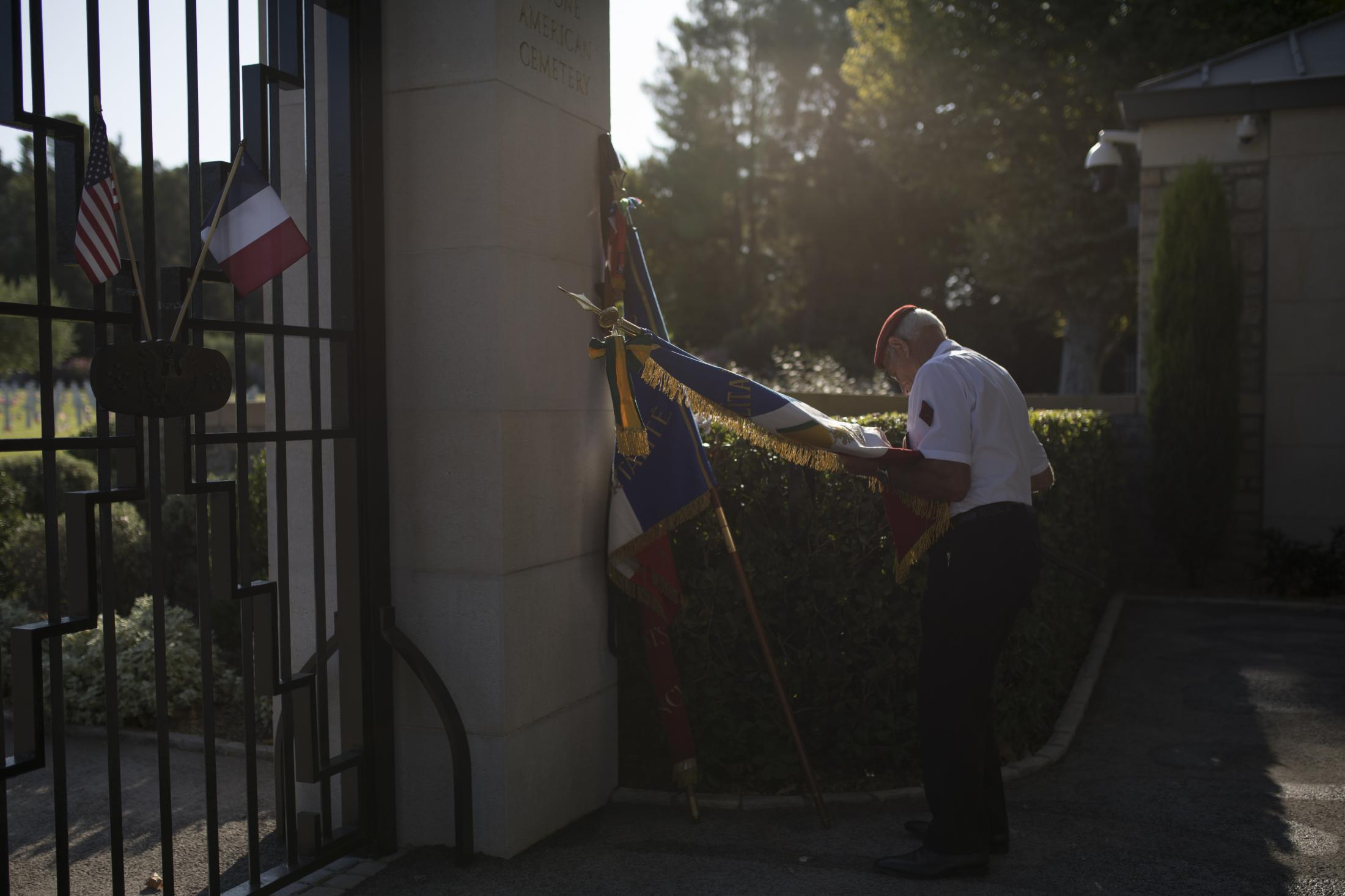 A veteran adjusts a French flag before a ceremony at the Rhone American Cemetery in Draguignan, southern France Friday Aug.16, 2019, as part of the commemorations to mark the 75th anniversary of the Allied landings in the South of France. The event will remember Operation Dragoon, which enabled the liberation of France from Nazi occupation. (AP Photo/Daniel Cole)