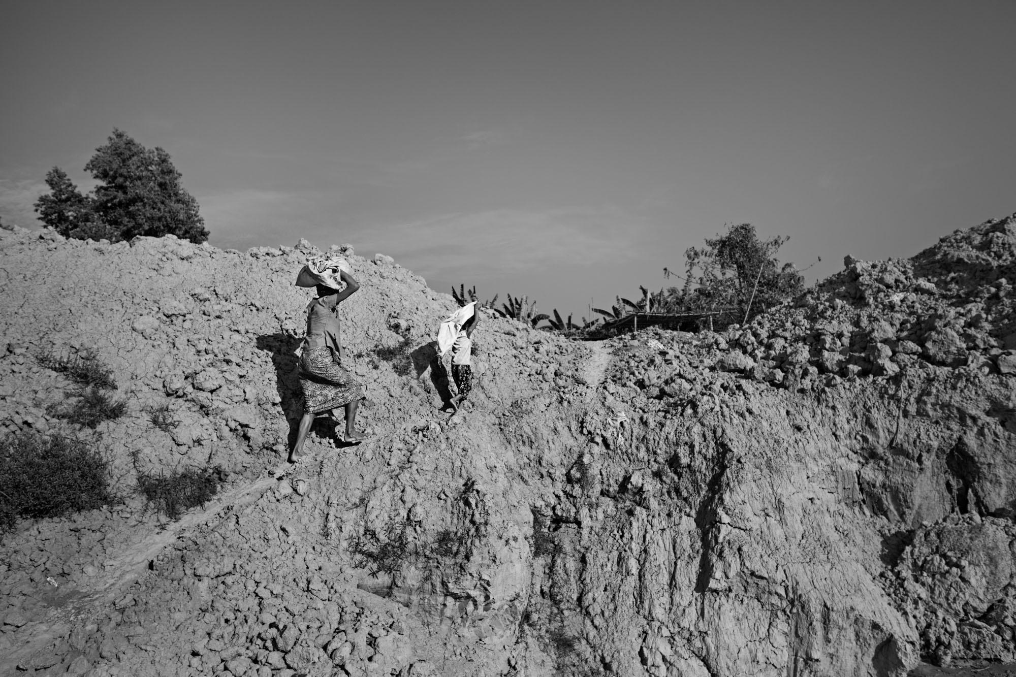 Than Nwe and her daughter, Saung Ning Wai, carry sacks of clay up the embankment from a machine-dug pit to the small shack where their family fashions bricks.